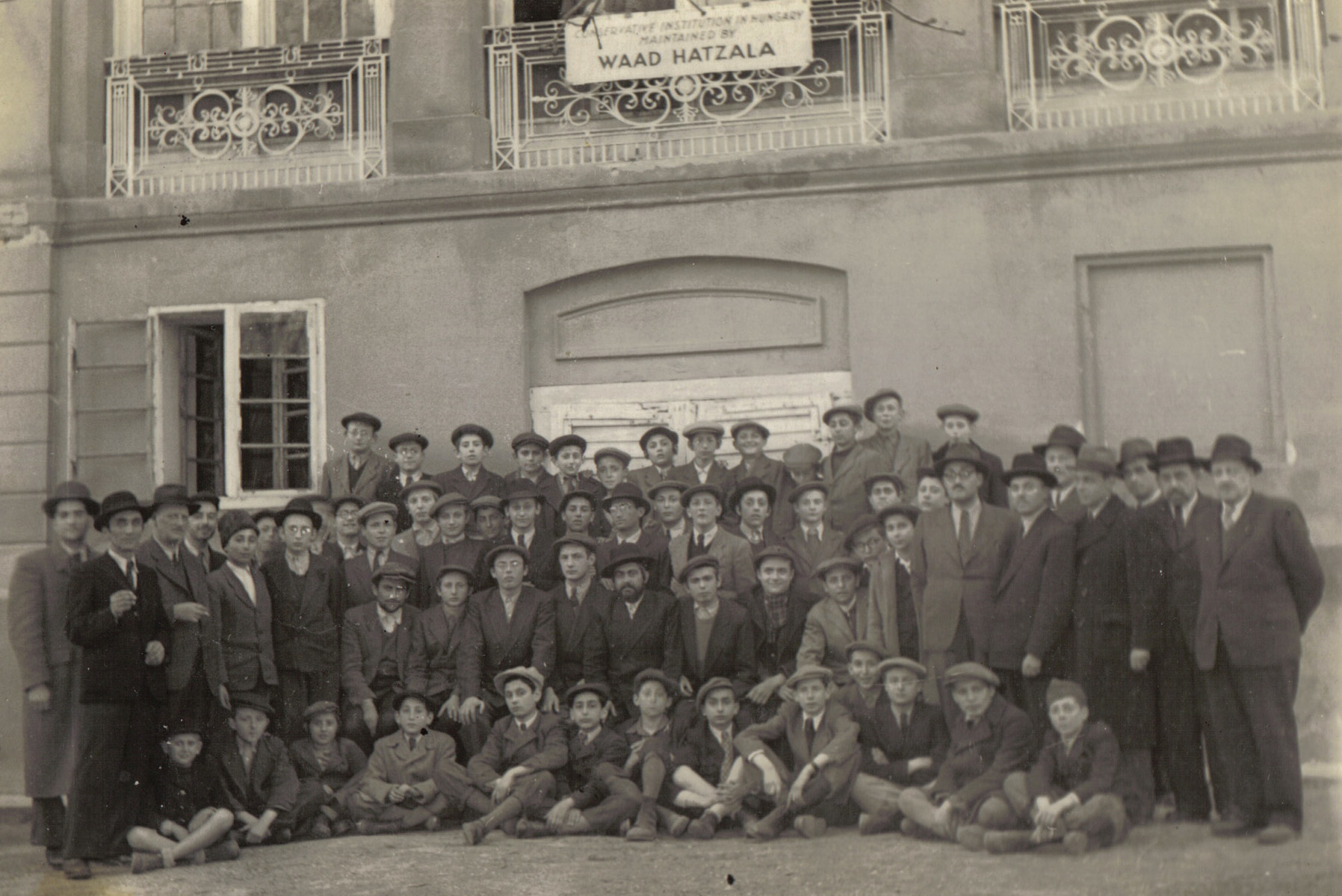Group portrait of Orthodox men and boys outside a building sponsored by the Vaad Hatzala in Hungary.