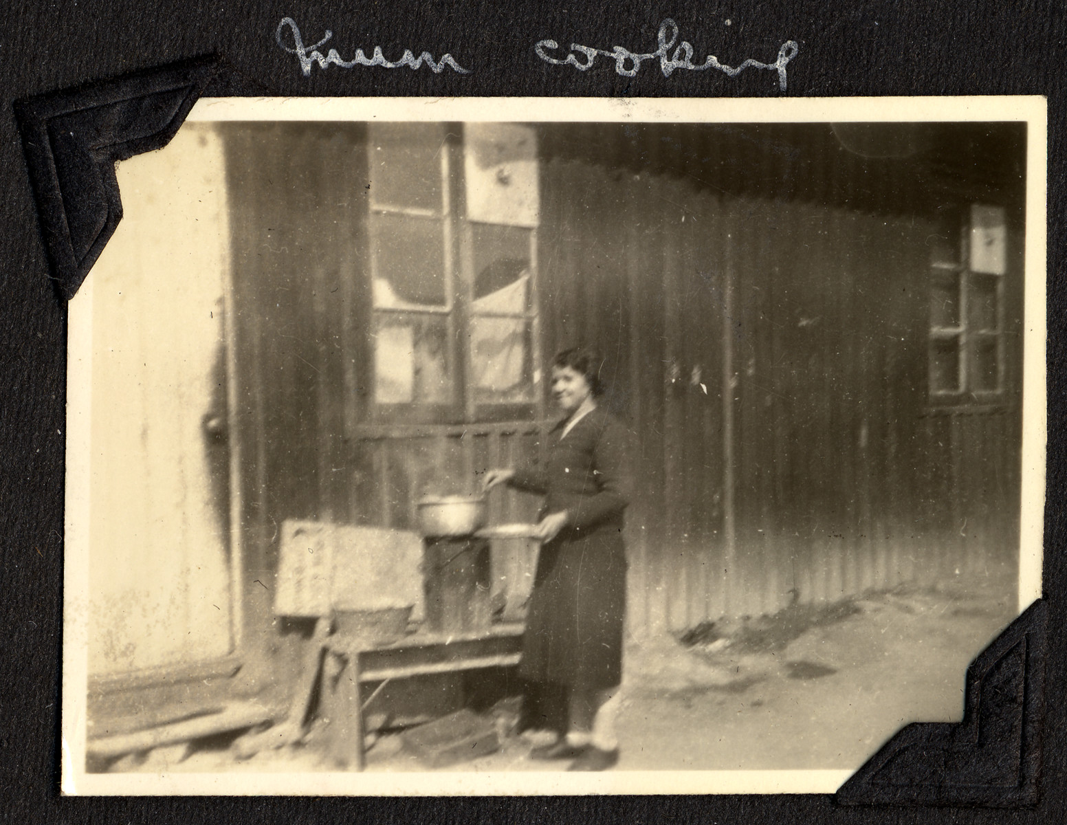 "A woman cooks on an outdoor makeshift stove in the Ash Colony in Shanghai.  The original caption reads: ""Mum cooking."""