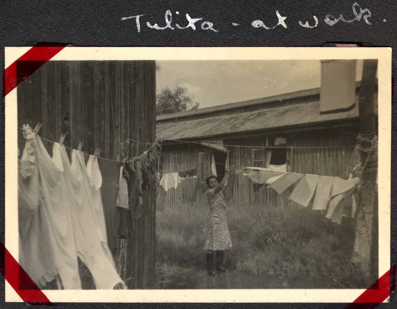 "A woman hangs laundry up to dry in the Ash Colony in Shanghai.  The original caption reads, ""Tulita - at work."""