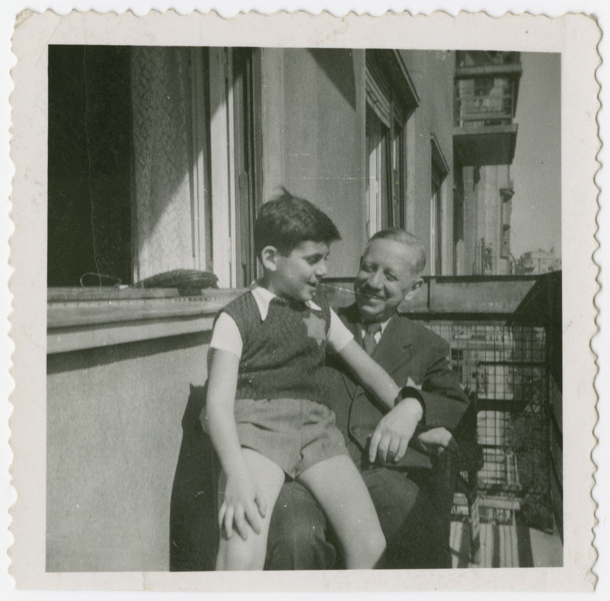 Otto Veidlinger, sits on the lap of his father, on the balcony of their apartment; in Budapest; both are wearing Jewish stars.