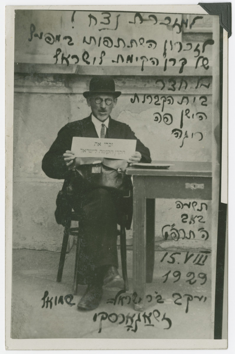 "Yaakov Zagorski sits outside the Jewish cemetery in Riga holding a sign for Keren Kayemet (Jewish National Fund).  Yaakov Zagorsky was a prominent Jewish  public figure in Riga, a collector of Jewish periodicals, and the creator of a ""museum of Jewish press.""   The original caption reads ""As an eternal remembrance!  In memory of your participation in the work of Keren Kayemet of Israel In front of the old Jewish cemetery in Riga."""