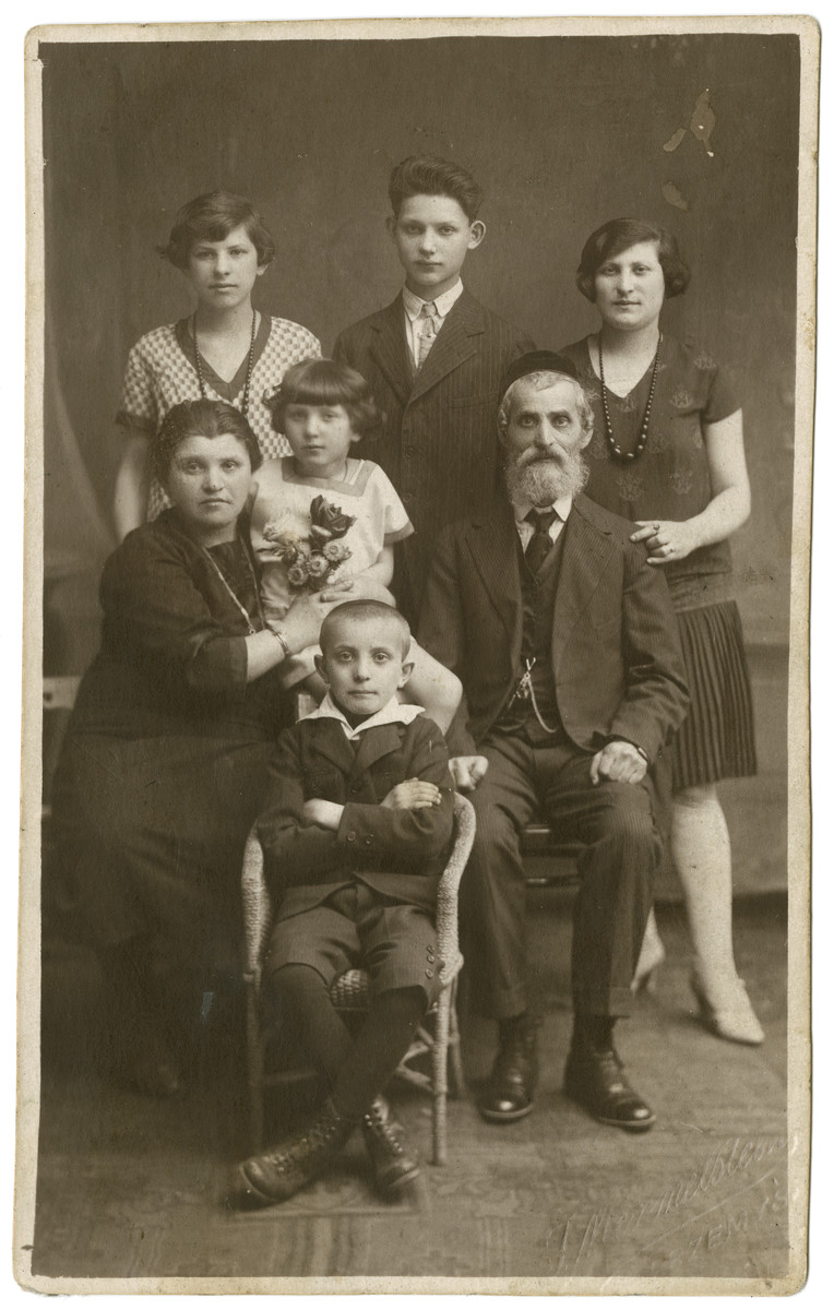 Ita and Don Mordechai Adam pose for a portrait with their children.   Standing (L to R) are the couple's elder children Fraidel, Sam, and Hinde. The couple's younger children Kaila (center) and  Moshe (seated) are also pictured.