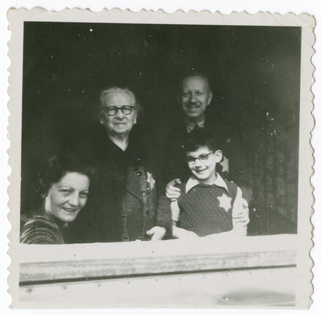 The Veidlinger family poses in their home in Budapest wearing Jewish starts.  From left to right are a friend of the family, Fanny Weidlinger, Andrew Veidlinger and Otto.