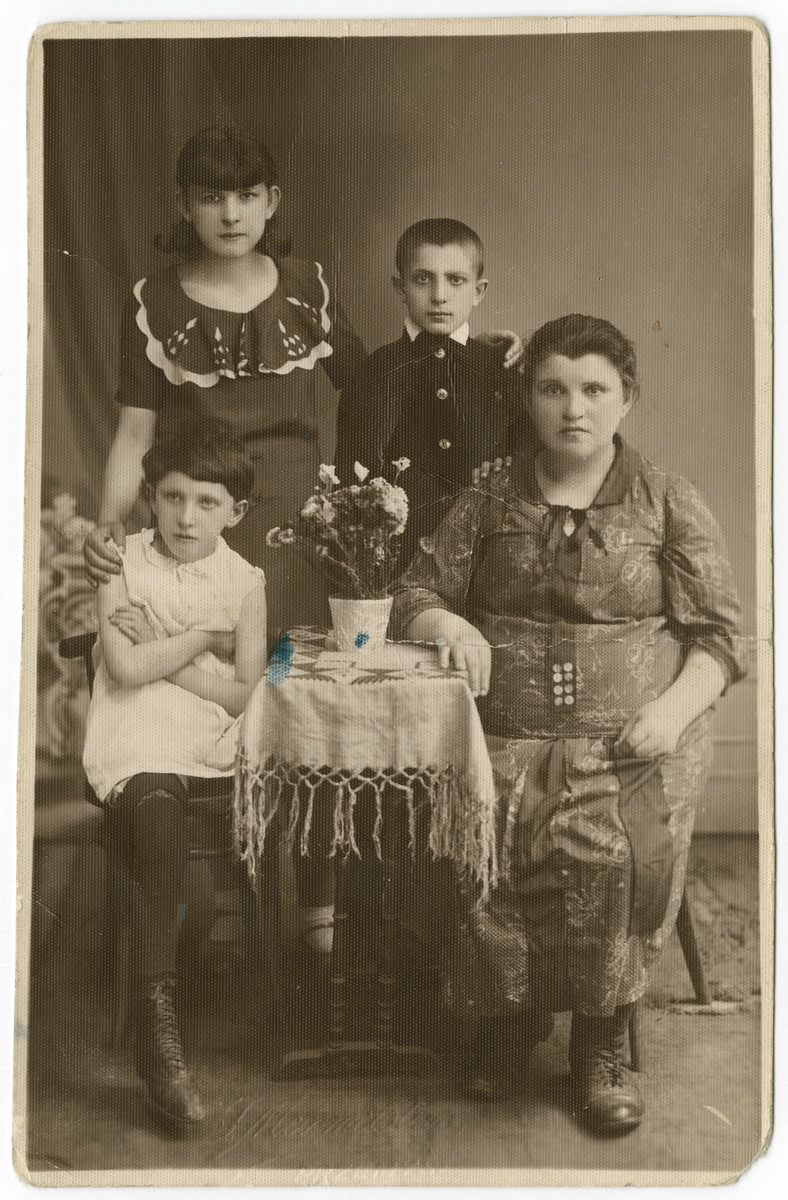 Studio portrait of the Adam family of Pryzemysl, Poland.   Pictured are Ita Adam and her children, Fraidel and Moshe (standing), and Kaila, (seated).