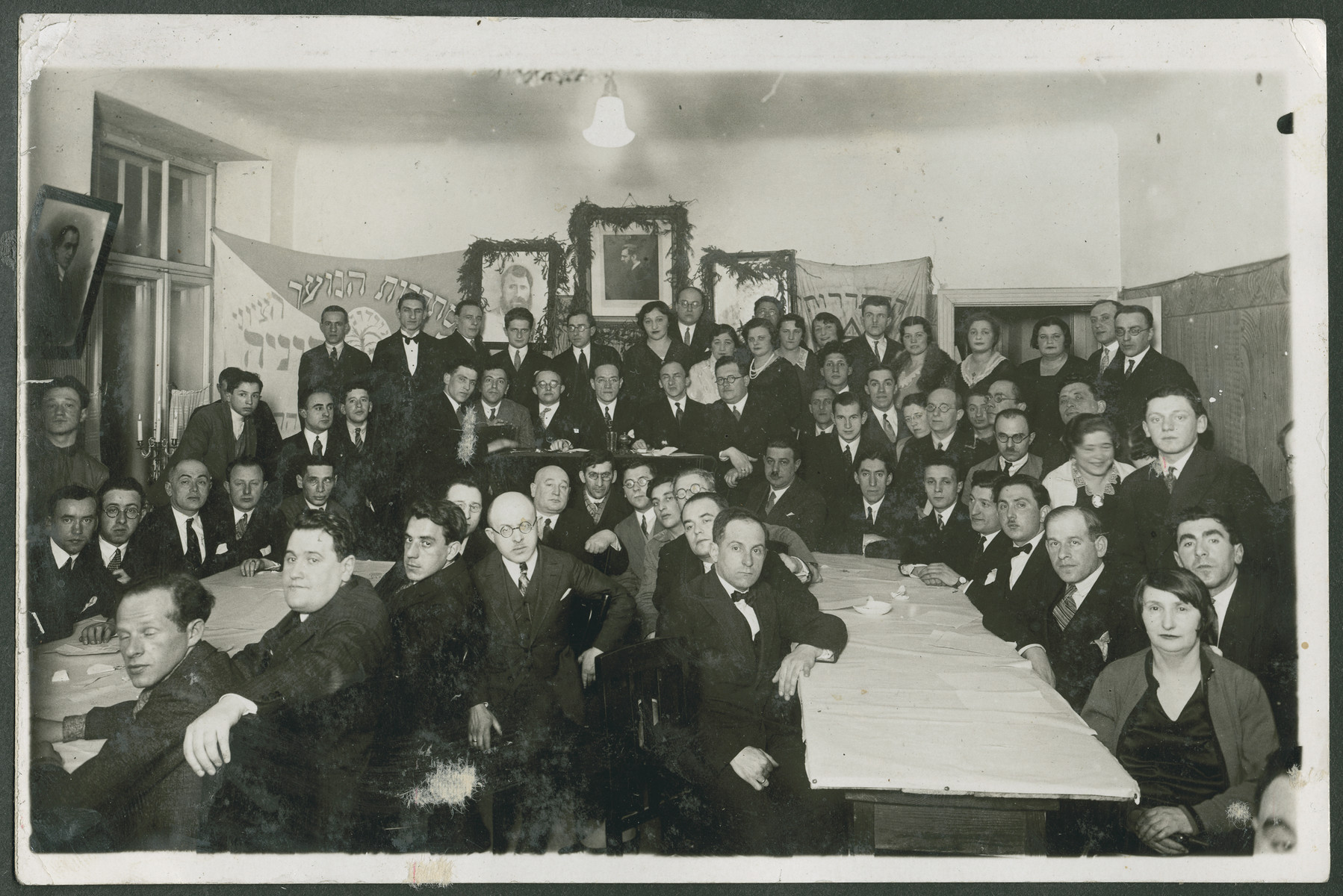 Meeting of a Zionist group in either Latvia or Lithuania.    Zionist flags and a portrait of Theodor Herzl hang on the walls.  Samuel Gotz is pictured in the front, second from the left.