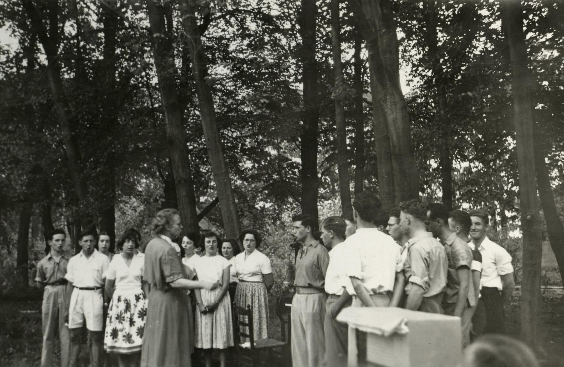 Zionist youth sing outdoors in a hachshara in postwar Holland.