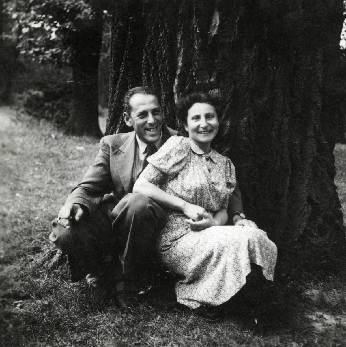 Emil and Elze Goldberg sit outside on the grass in postwar Szczecin.