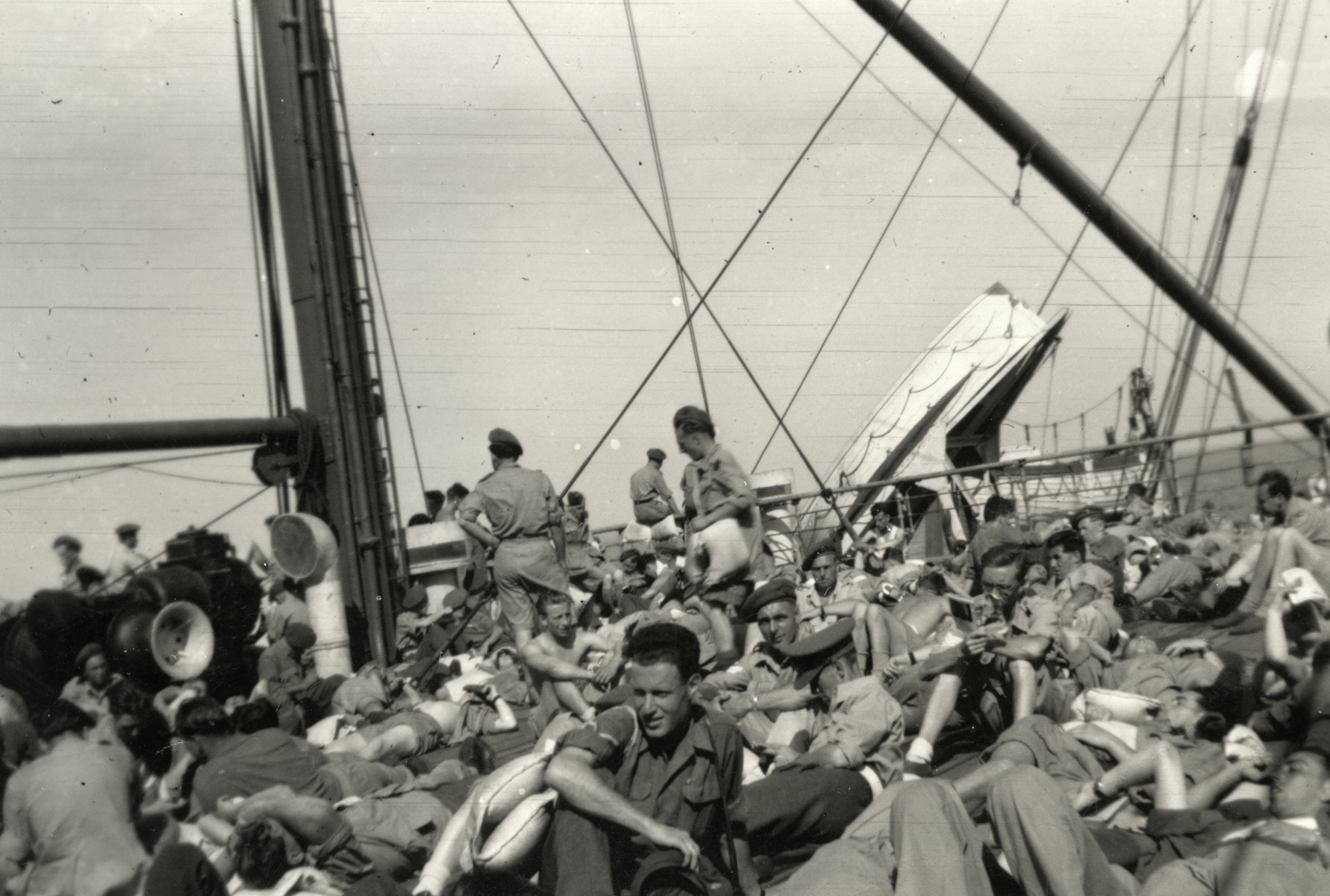 Passengers lie on the upper deck of a ship bound for Italy.
