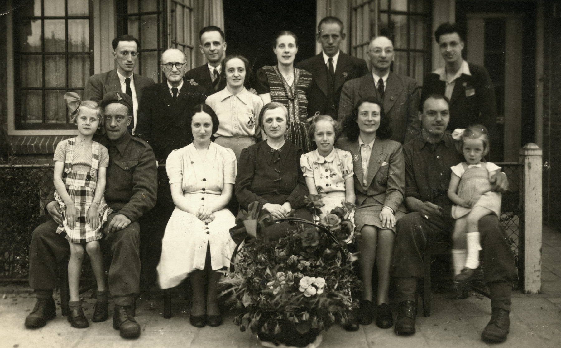 Ellis Cohen-Paraira poses with her rescuers, the Kooistra family, shortly after liberation.   Seated left to right are Annika Kooistra sitting on the lap of a British soldier, Lien Gans, Mrs. Gans, Rommy Kooistra, Ellis Cohen-Paraira, Henry (a British Jewish soldier) and Riki Kooistra.  Standing are Hank Gans, Mr. Gans, David Cohen-Paraira, Mien Cohen Schpektor, Wopke Kooistra, Heilje Kooistra, Mr. Pam, Bram Cohen-Paraira.  The Gans family also hid at the Kooistra home.