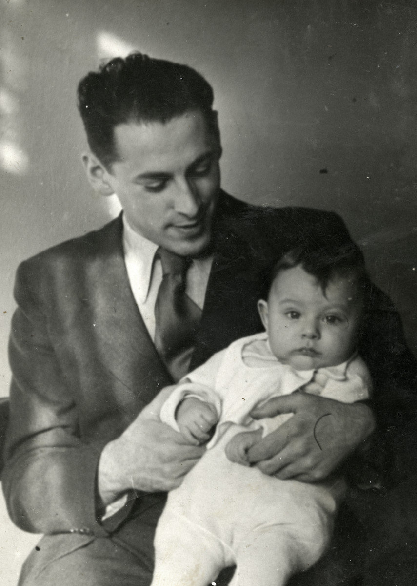 Studio portrait of Emil Goldberg holding his baby son Edwin (Edik)