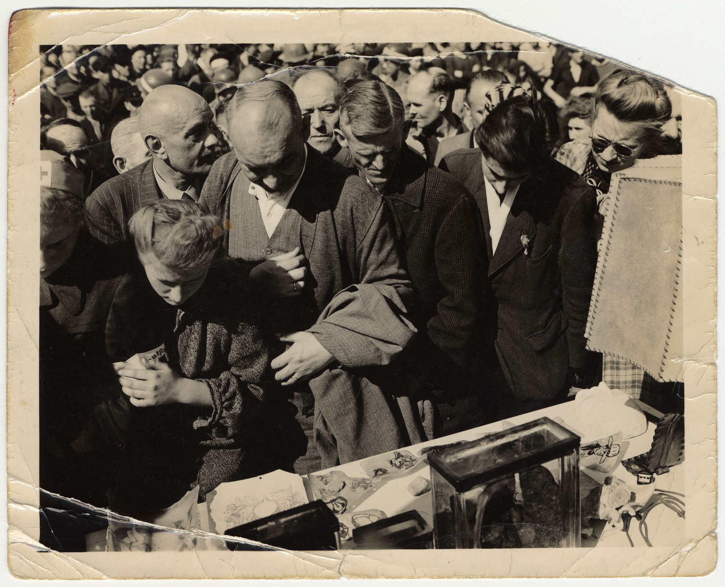 """German civilians are forced to look at a display in the Buchenwald concentration camp of tattoos and a lampshade allegedly made from human remains.  The original caption reads: """"...German civilians going through the concentration camp.  On the table are the tattoos.  Whenever anybody had a tattoo on him, they'd cut the skin out and treat it and then make lamp shades and things like that.  You can see one lamp shade.  The glass jar on the table has lungs in it.  They also did a lot of experimenting on these slave laborers by injecting serums and diseases into them."""""""