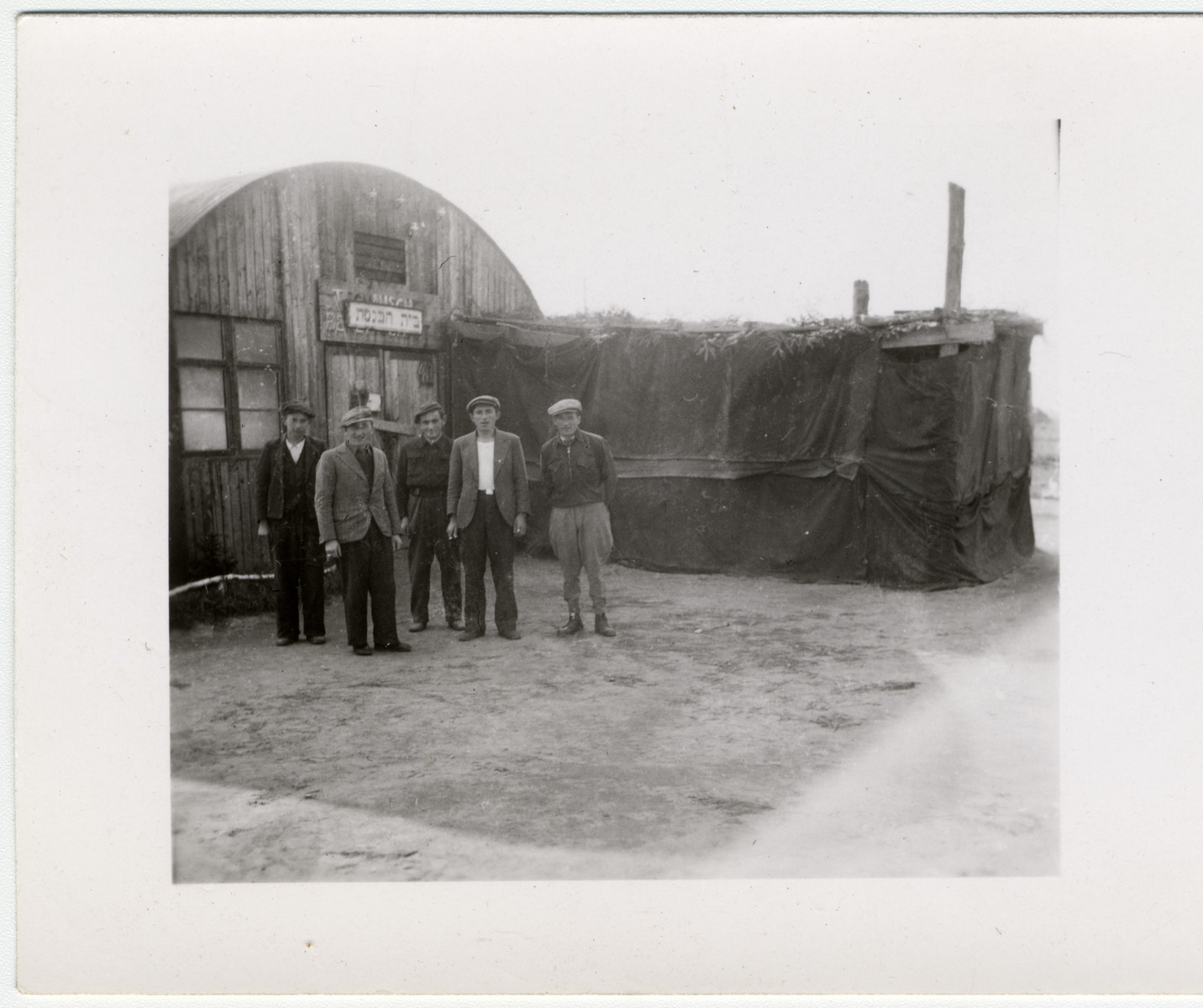 Five men stand in front of a makeshift synagogue in a Quonset hut and sukka [probably in Babenhausen].