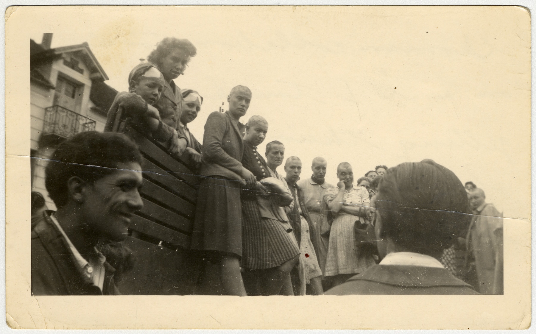 "French women accused of collaboration are publicly humiliated by having their heads shaved.  The original caption reads: ""German collaborators on a G.I. truck, after getting their hair shaved off.  The French did this in every town."""