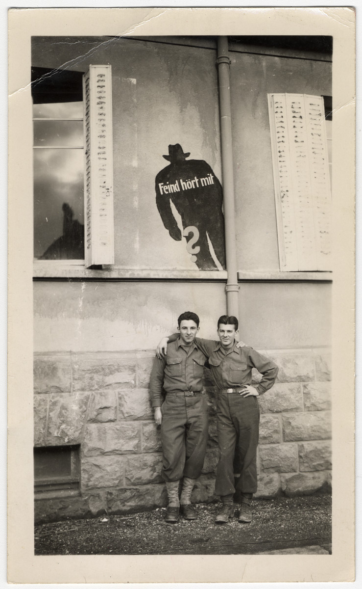 """Two American soldiers pose underneath a poster that shows a lurking silhouette and a German caption that reads """"The enemy is listening."""""""