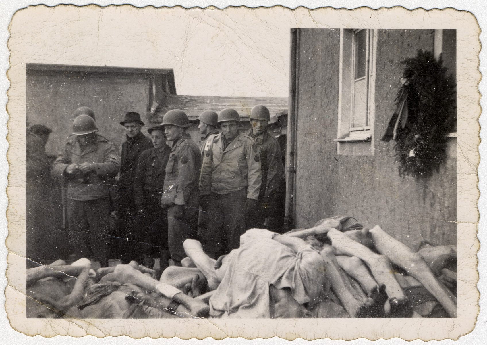 "American soldiers examine the pile of corpses outside the Buchenwald crematorium.  The original caption reads: ""A view of the concentration camp of Buchenwald (Weimar) Germany.  John Truty is in the foreground."