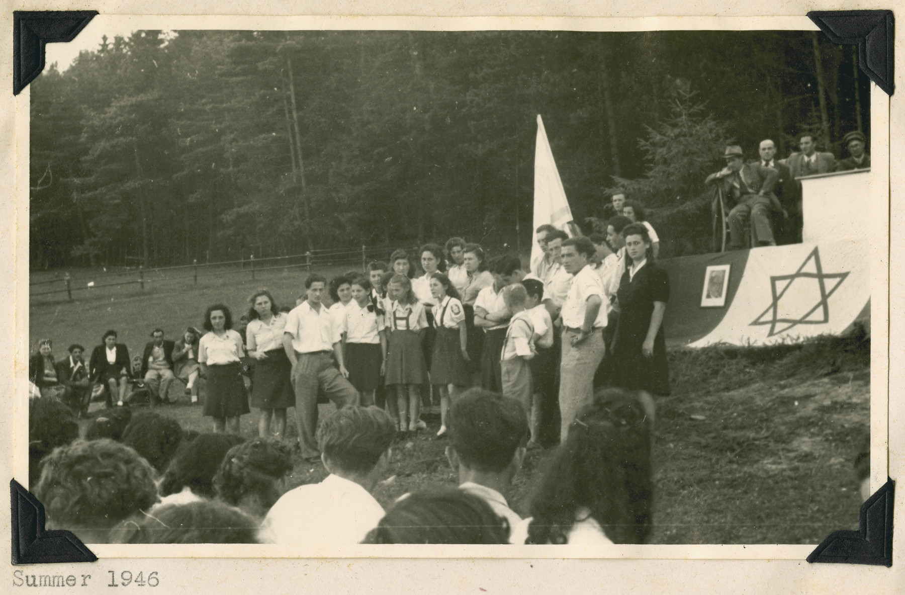 "A young girl sings the partisan song at an outdoor gathering in Kibbutz Buchenwald.  The original caption reads: ""A solo performance.  The choir rests while a little girl sings, ""Don't say this is your last journey,"" the song of the Jewish partisans."
