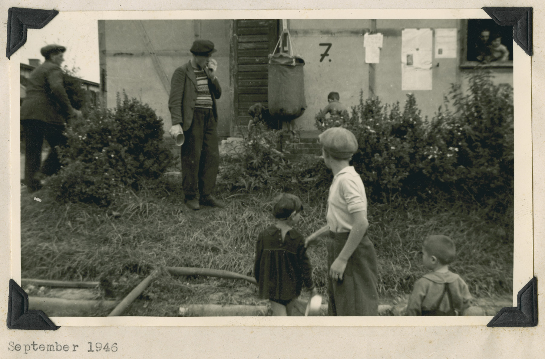 "Men and children stand outside a building in the Ziegenhain displaced persons camp.  Hanging from a hook on the outside of the barrack is a bag for water.  The original caption reads: ""Ziegenhain.  Lister bags: The only water supply for Ziegenhain upon its conversion into a Jewish Refugee camp."""