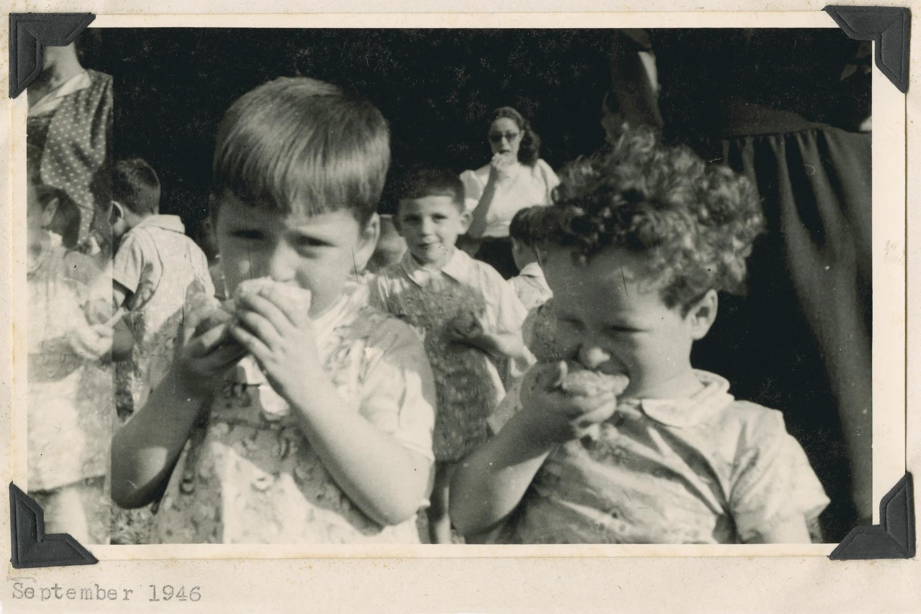 "Two young children from the Lindenfels school enjoy slices of orange.  The original caption reads: ""Lindenfels school.  A foretaste of Eretz Israel: Oranges."""