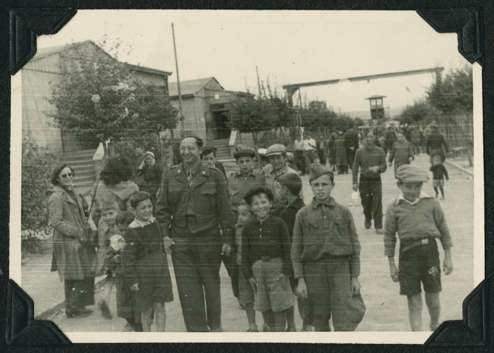 Children from the Ziegenhain displaced persons camp walk down a street together with David Bar-El, a member of the Frankfurt Jewish GI Council.  A watch tower can be seen in the background.