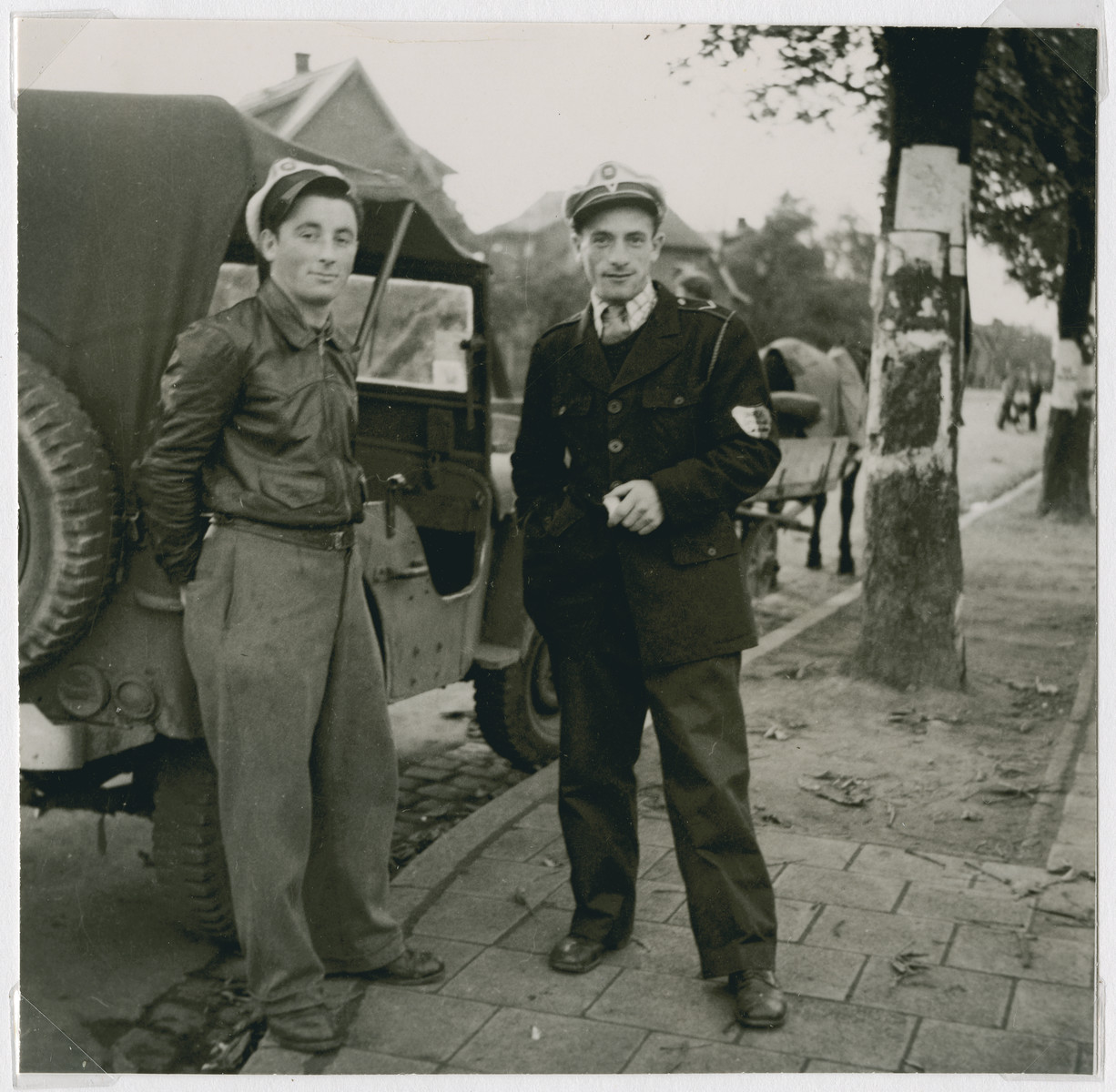 Two Jewish policemen in the Zeilsheim displaced persons camp stand next to a truck.