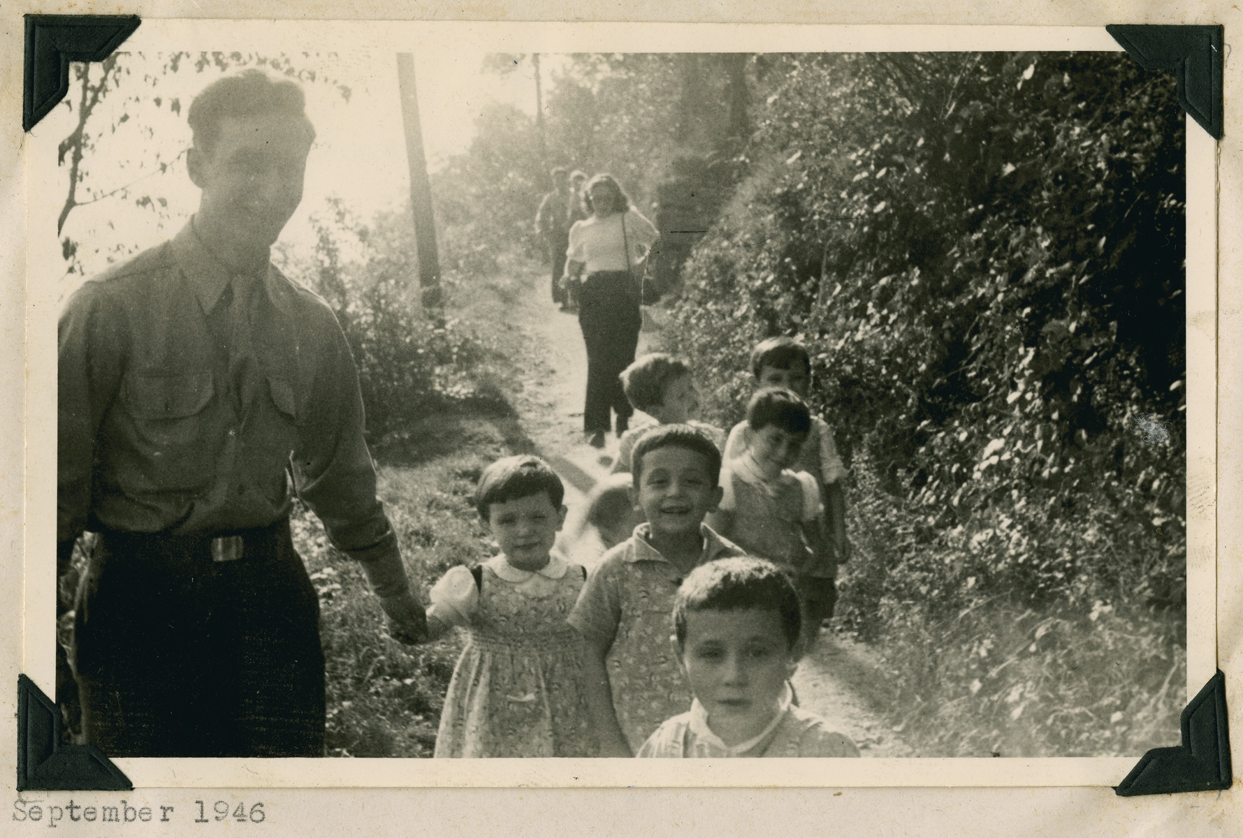 """A member of the Frankfurt GI Council takes young children for a walk in Lindenfels.  The original caption reads: """"Lindenfels school.  Visitors show the hosts around."""""""