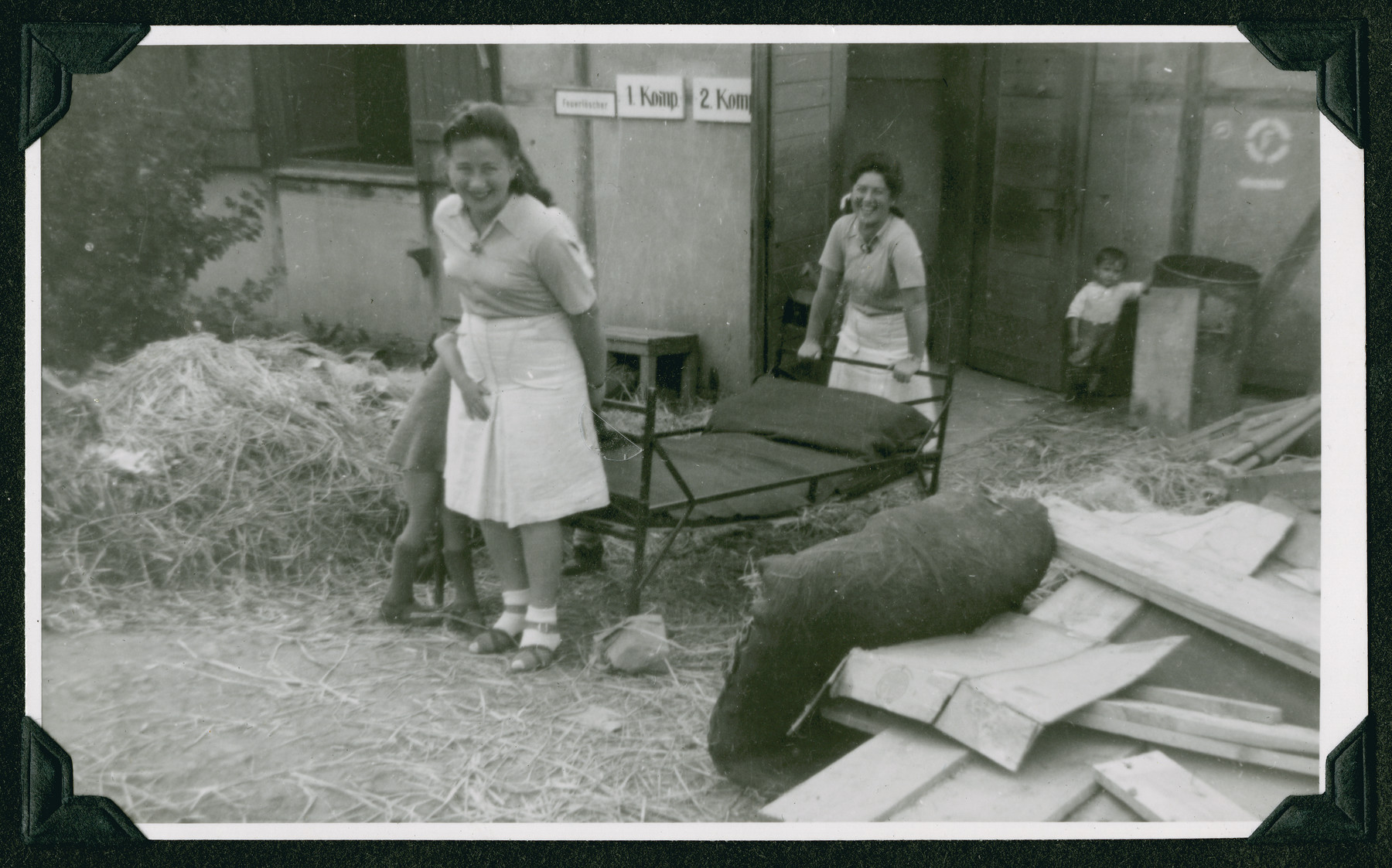 "Two women carry a bed past a pile of lumber during the clean-up of the Ziegenhain displaced persons camp in order to make it liveable.  The original caption reads: ""What confronted the Jewish Displaced Persons when they were brought to Ziegenhain."""