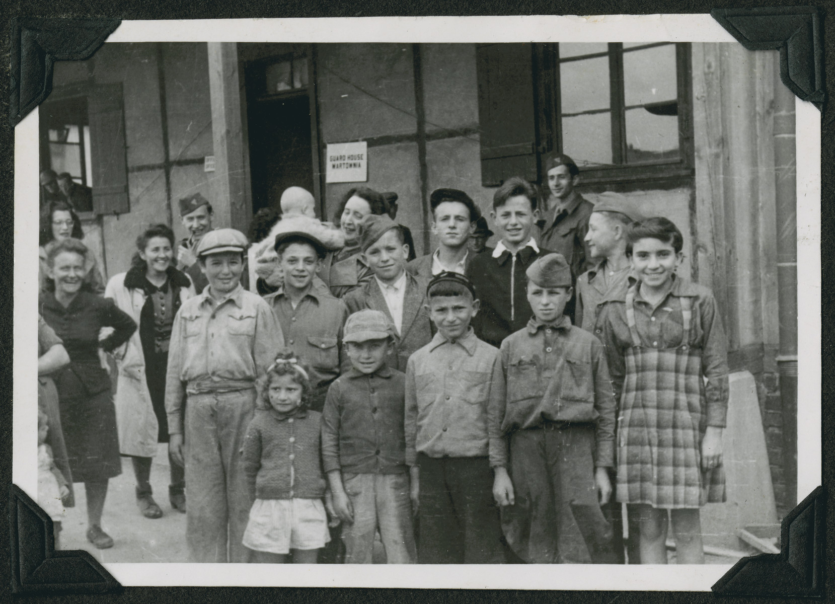 Members of the Frankfurt Jewish GI Council pose with children and women in the Ziegenhain displaced persons camp.  Eliezer Dembitz is at the top left and David Marcus is at the top right.