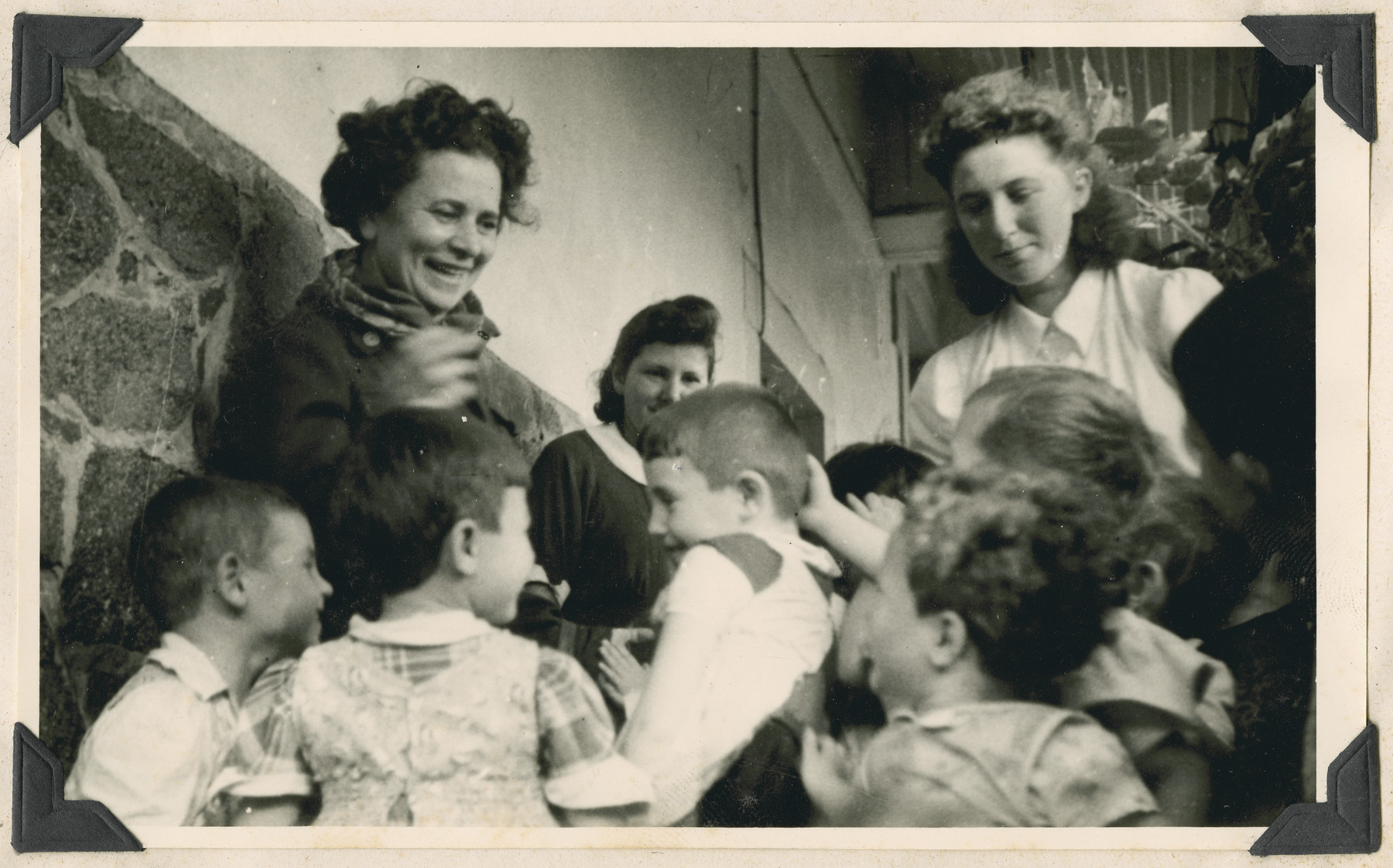"""Women and children in the Lindenfels school near Frankfurt.  The original caption reads: """"Lindenfels school.  In a small village in the beautiful Bergstrasse district.""""  Anda Pinkerfeld, a poetess from Palestine, is standing on the left."""