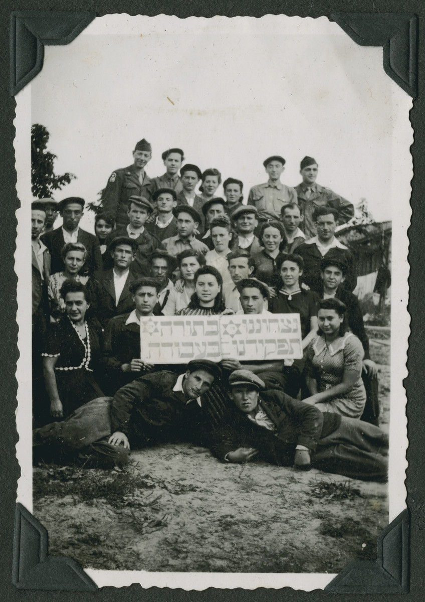 "Group portrait of members of the Mizrachi religious Zionist youth movement in the Ziegenhain displaced persons' camp holding a sign that reads, ""Our eternity is in Torah, our task is in work.""  Two members of the Frankfurt GI Council pose with them in the back row."