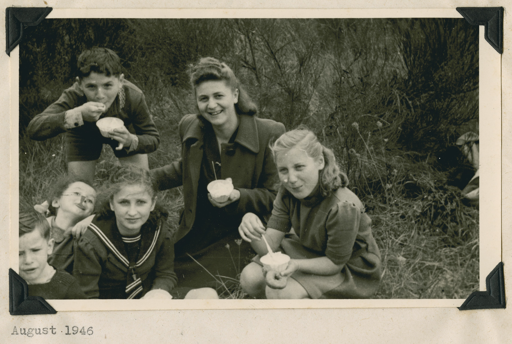 """Childern [probably from the Lindenfels schoool] enjoy an ice cream picnic.  The original caption reads: """"Autobahn near Frankfurt Picnic: The smiles of contentment."""""""