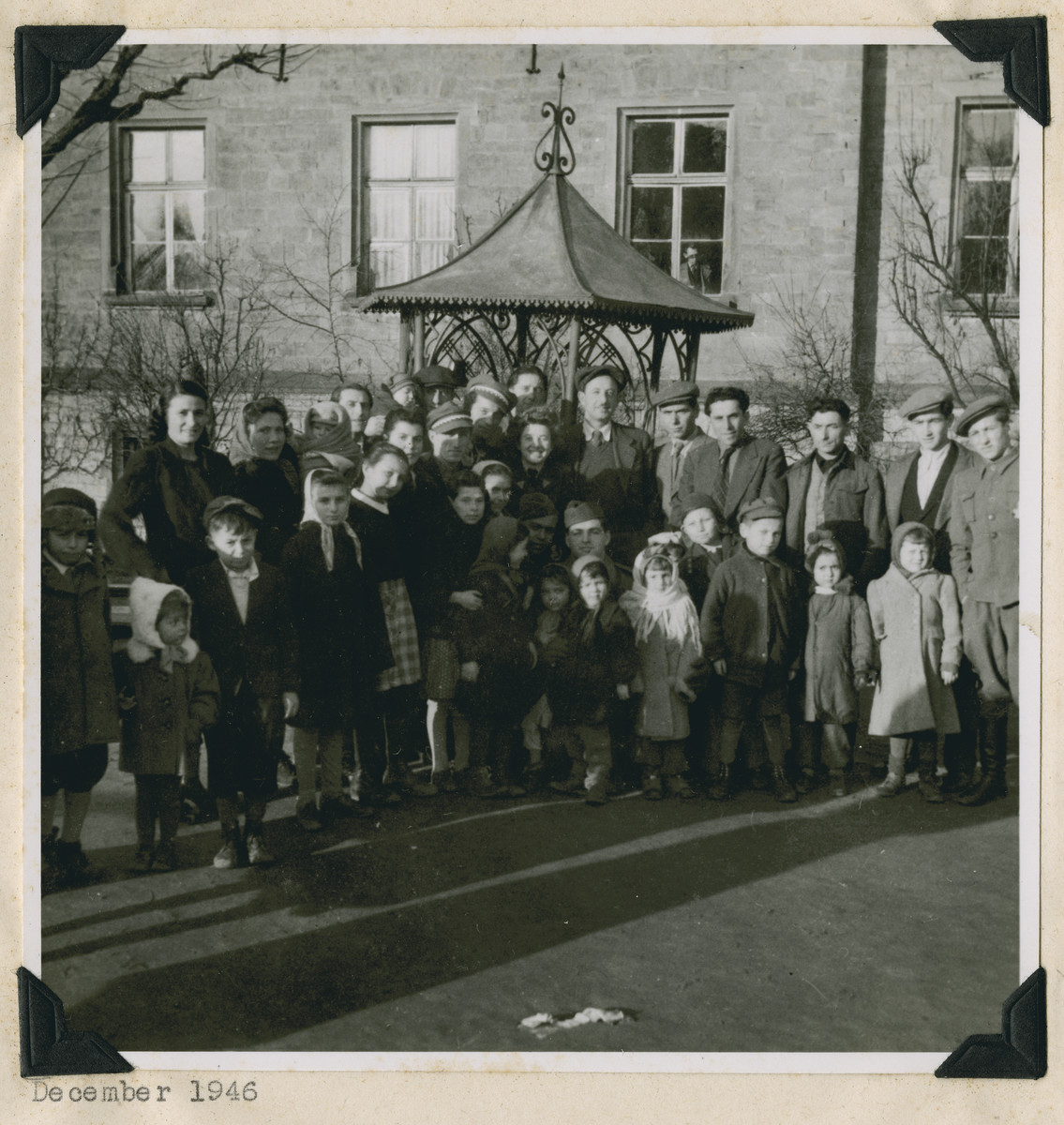 "Group portrait of residents of the Dieburg displaced persons camp,  The original caption reads: ""Dieburg.  Look at the birdie folks."""