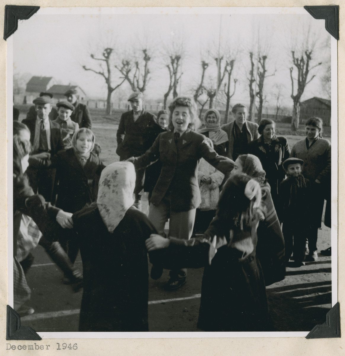 "Members of the Frankfurt GI Council dance with children in the Dieburg displaced persons camp.  The original caption reads: ""Dieburg.  Youthful hands clasp each other firmly as they sing 'David Melech Yisrael' and twirl the Hora."""