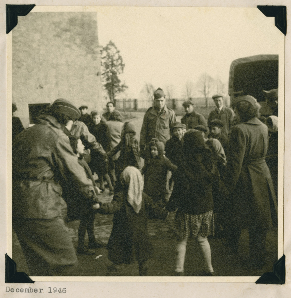 """Members of the Frankfurt GI Council dance with children in the Dieburg displaced persons camp.  The original caption reads: """"Council members join the children in the Jewish National dance -- the Hora."""""""