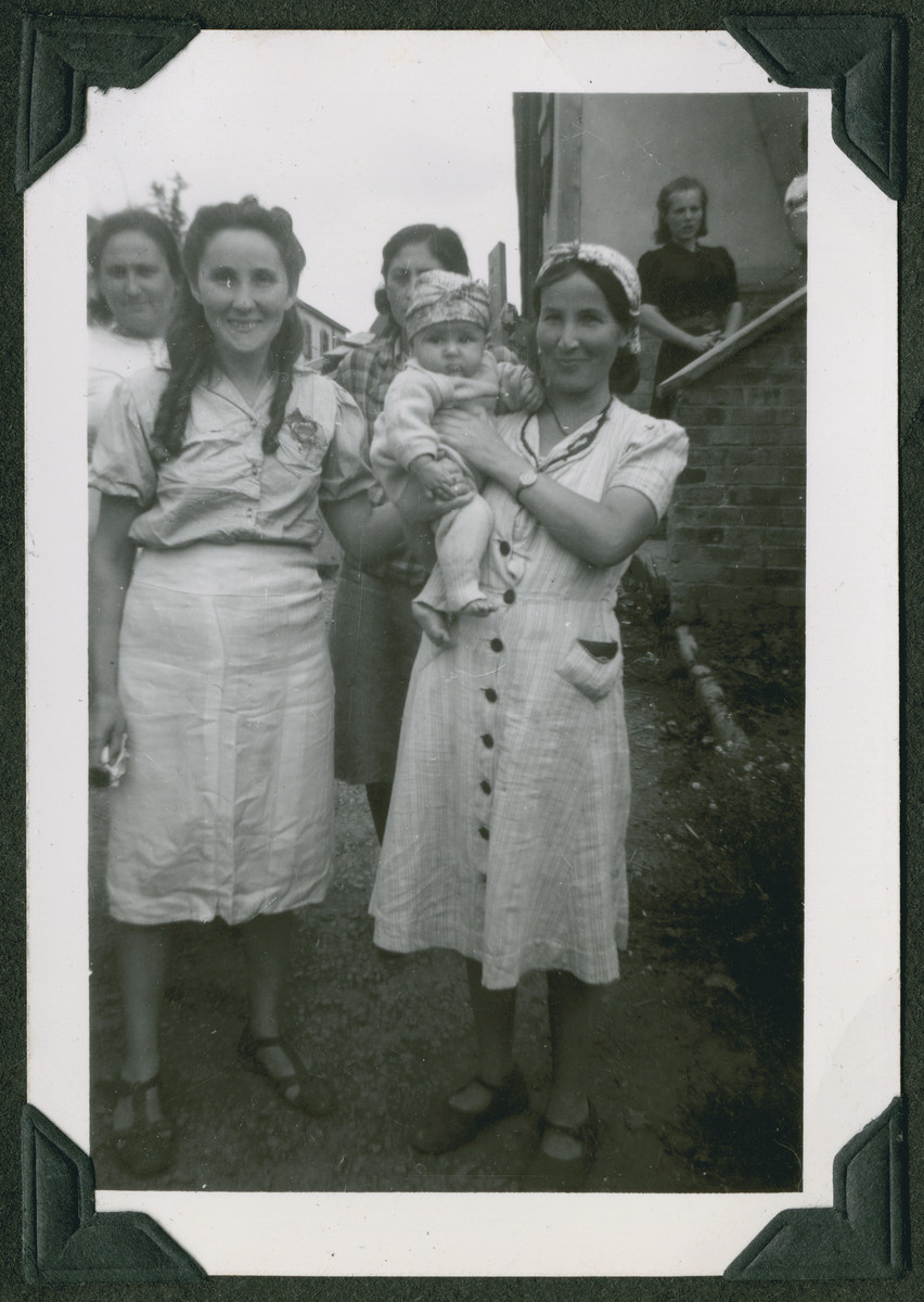 Group portrait of young women, one holding an infant, in the Ziegenhain displaced persons camp.