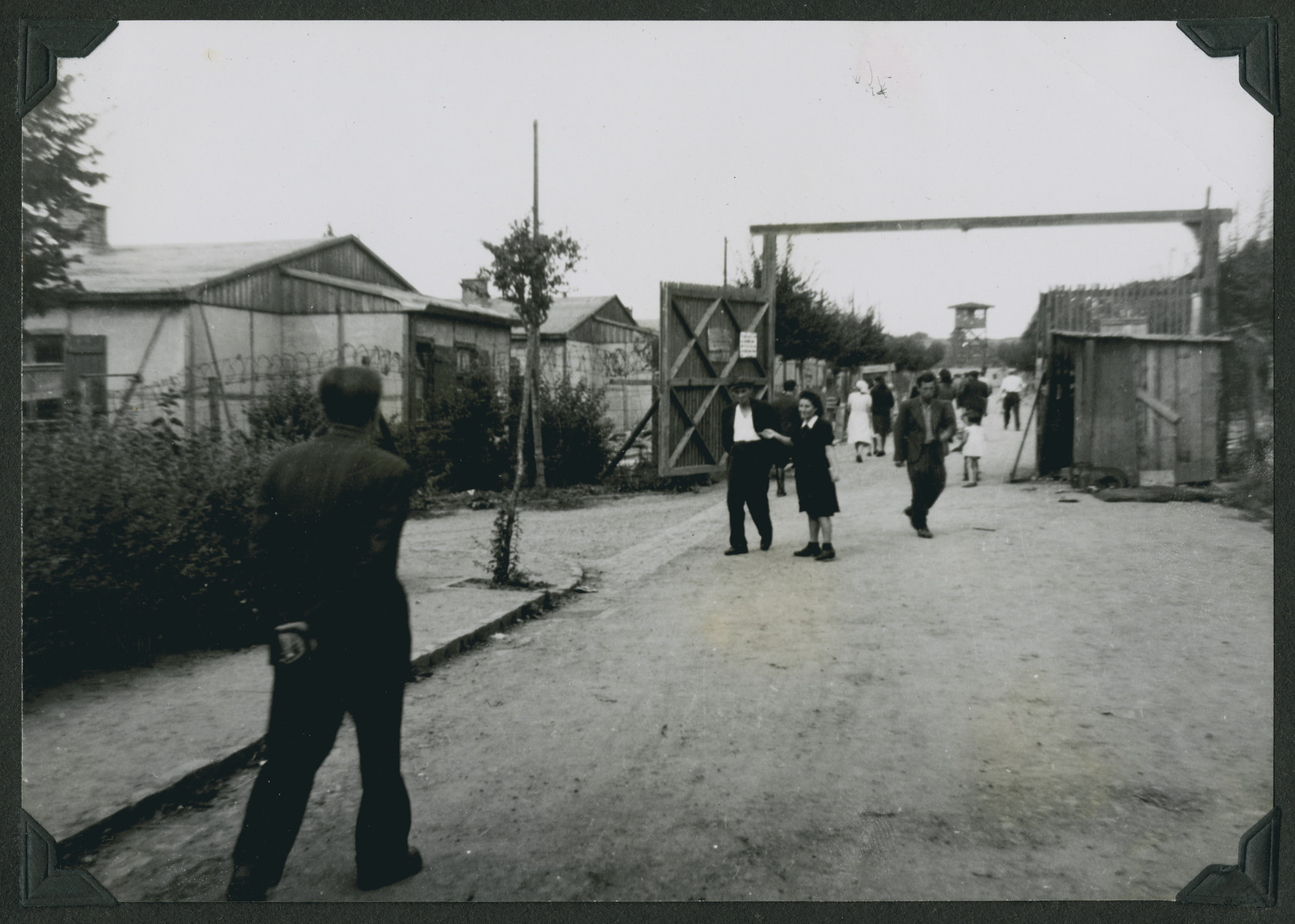 "Jewish displaced persons enter the main gate of the Ziegenhain displaced persons camp.  The original caption reads: ""Ziegenhain.  This is the gate for refugees.  Enter here and you shall suffer. -- the inner gate of the camp."""