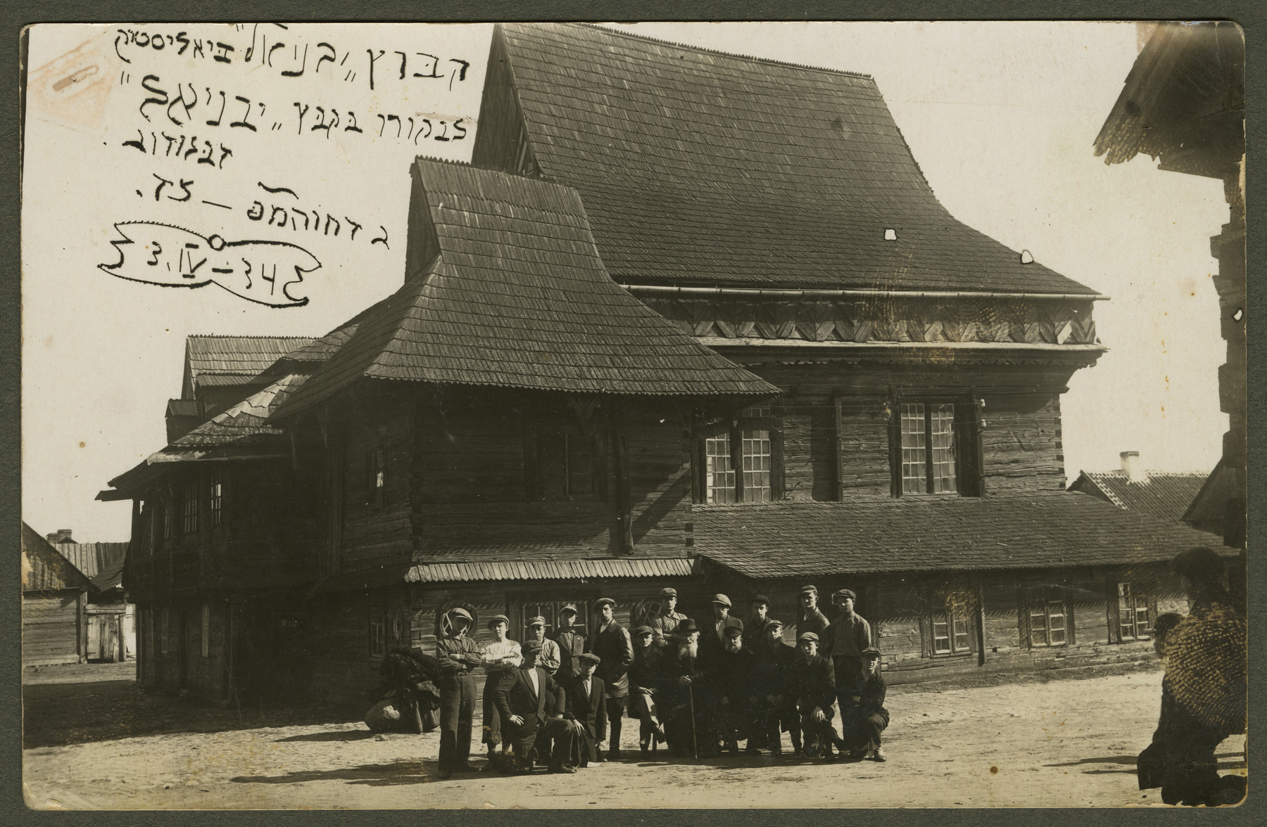 Members of the Hechalutz Mizrachi hachshara Yavniel in Bialystok pose outside a wooden synagogue.