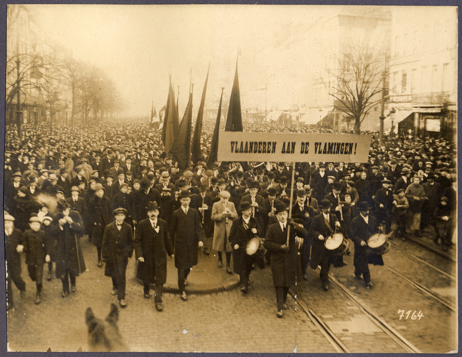 A large crowd parades through a city street carrying a sign the reads: Vlaanderen and de Vlamigen (Flanders for the Flemish).
