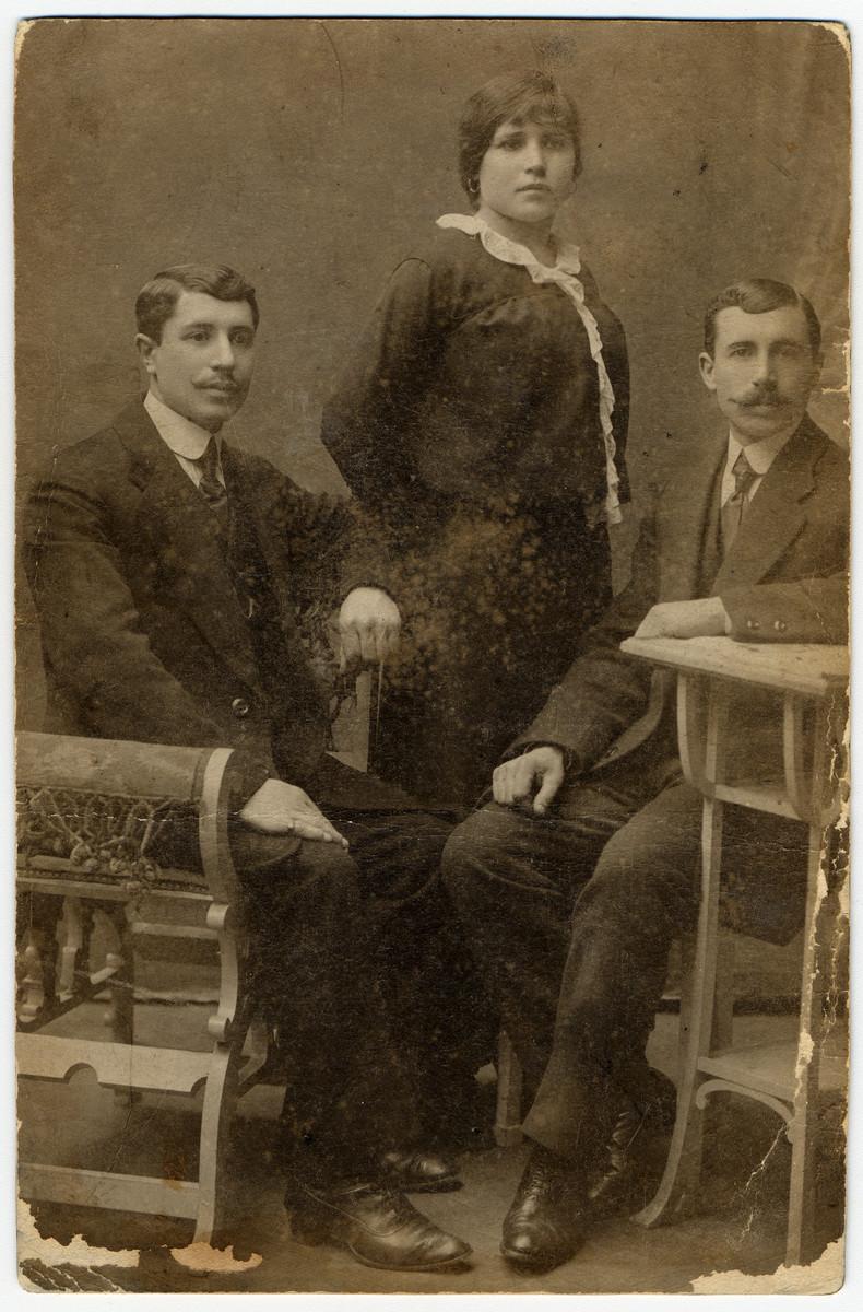 Studio portrait of Leja Blecher standing between her two brothers in Kelme Lithuania.