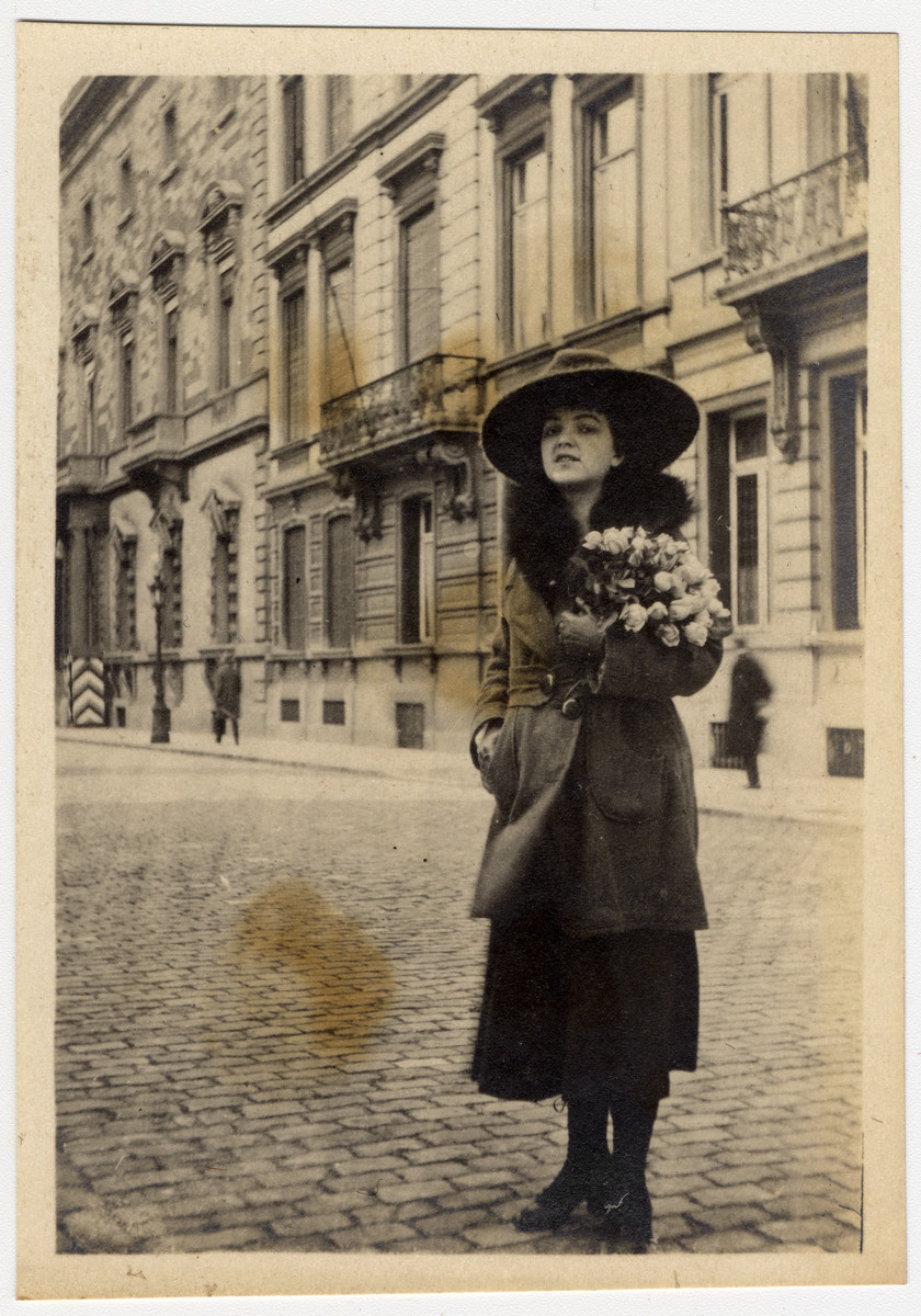 "Luise 'Lilli"" Lande stands on a street carrying a bouquet of roses."
