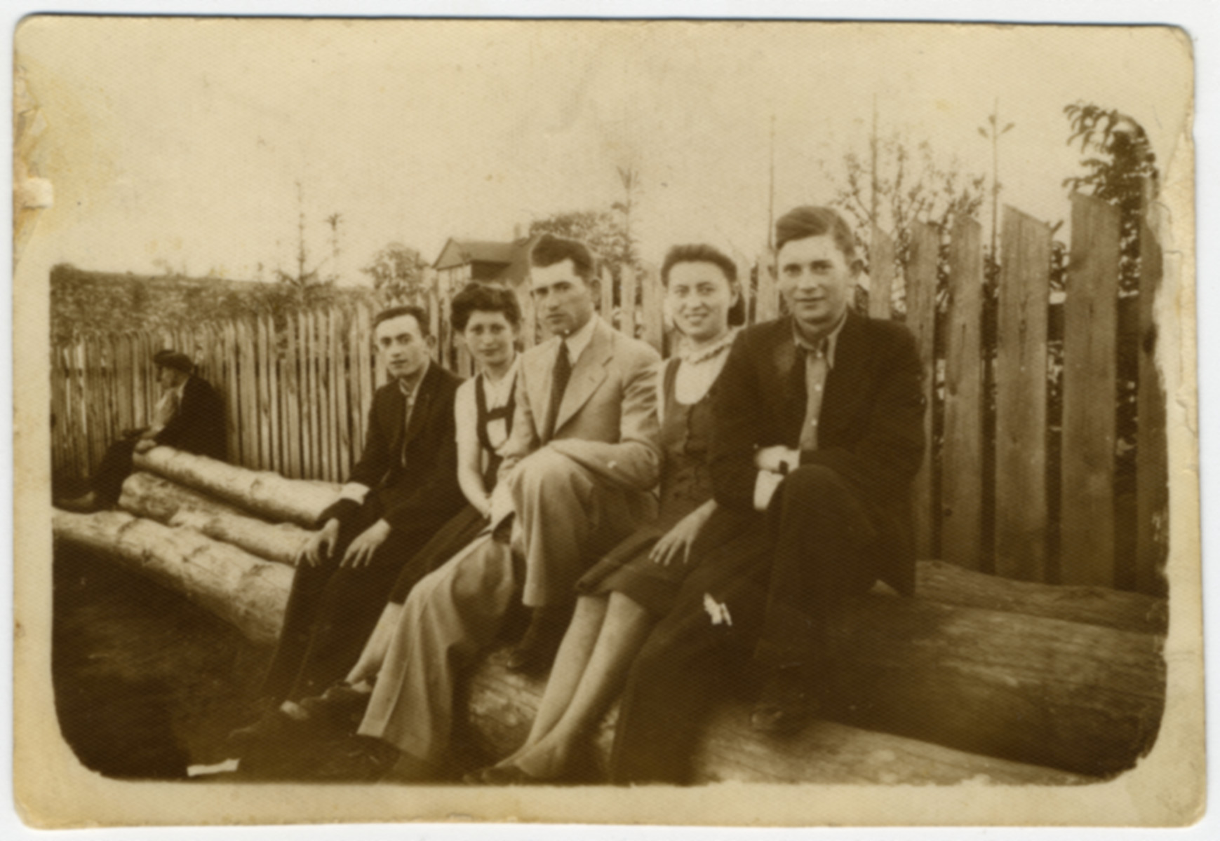 The Luksenburg family poses on some large logs shortly before the start of World War II.  Pictured from left to right are a friend (name unknown), Rivka, Mosche, (unidentified) and Kopel Luksenburg.