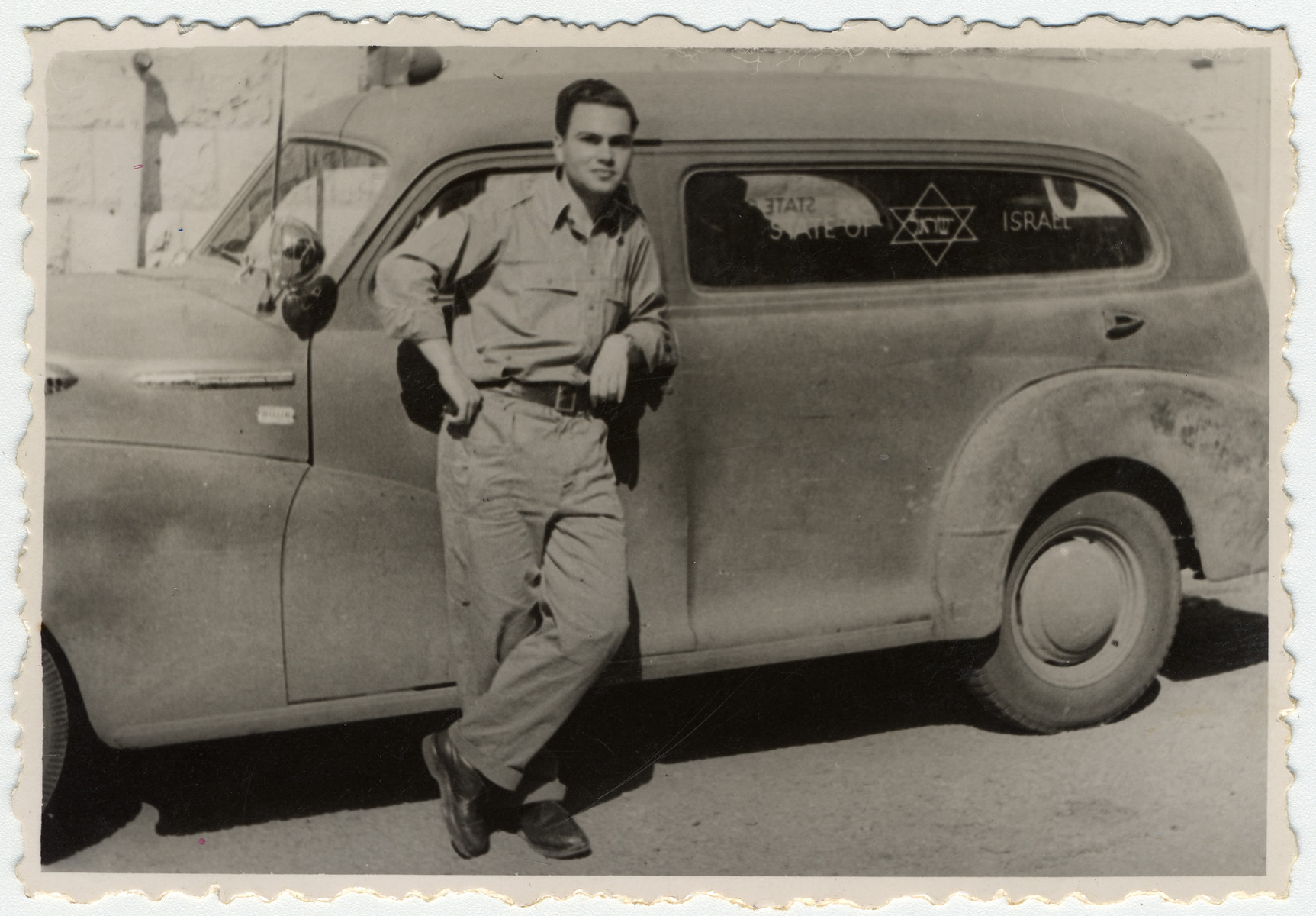 "Julius Menn, an soldier in the Israeli army, stands next to an automobile marked ""State of Israel""."