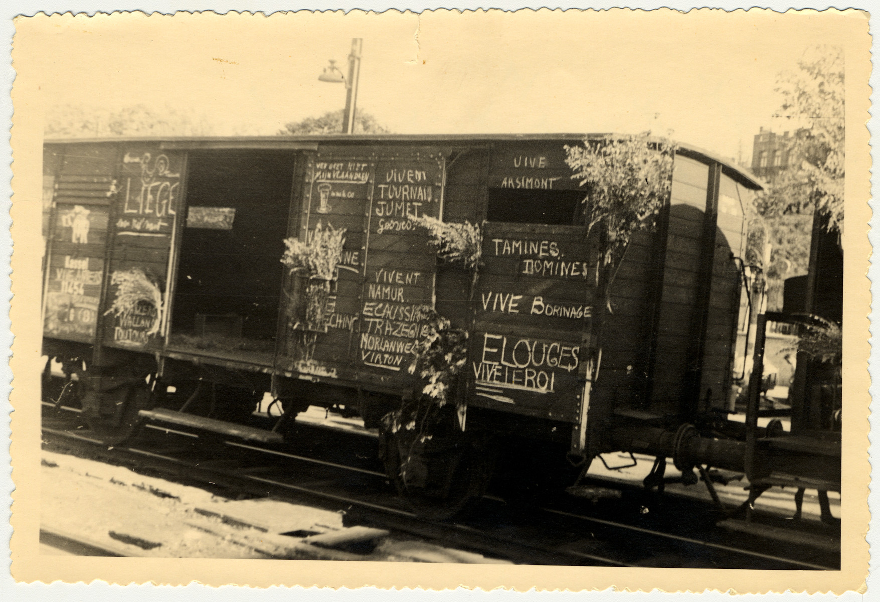 A photograph taken by Myron Moses showing a railcar after liberation in Namur, Belgium.  The empty railcar is covered in French graffiti.    Myron wrote on the back of the photo:  Mom and Dad -  Displaced personnel and prisoners of war are transported in these box cars.  The liberated French enthusiastically write 'vive's all over this car. Snapped in Namur, Belgium.  Love forever, Myron