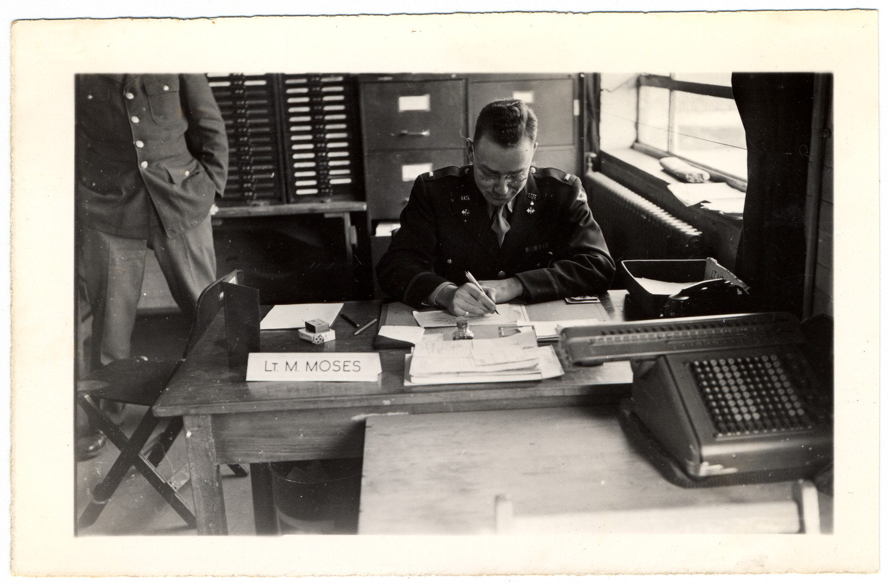 Lieutenant Myron Moses writes at his desk in the offices of the Signal Corps in Suippes, France.