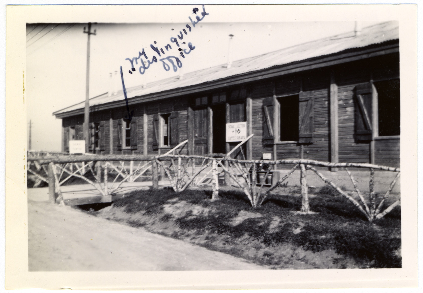 "A shack that housed the offices for the Signal Corps in Suippes, France.  Myron Moses worked there, and in the photo he demarcated the window to his office in the building.  On the back of the photo, Myron has written to his parents:   Mom 'n Dad -- This is our Signal ""shack."" The fancy [underlined in the caption] fence was set up by the POWs, under the architectural direction of Ralph Colton. Love, Myron"