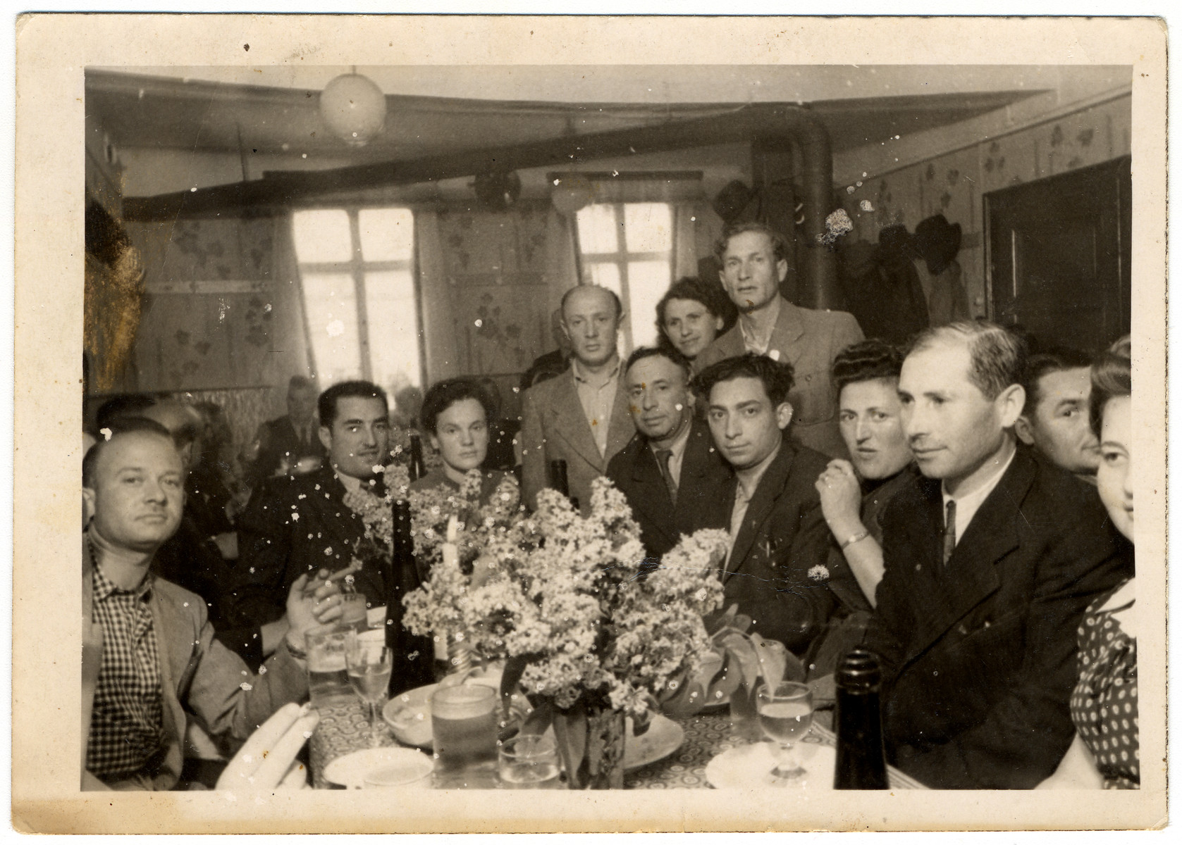 A group of displaced persons sits around a table in Zeilsheim following  a memorial service for victims of the Holocaust.  Roman Bol is pictured, standing in the back, on the right.  The man pictured second from the left has been identified as Leon Greenberg (later Green) of Gabin, Poland.