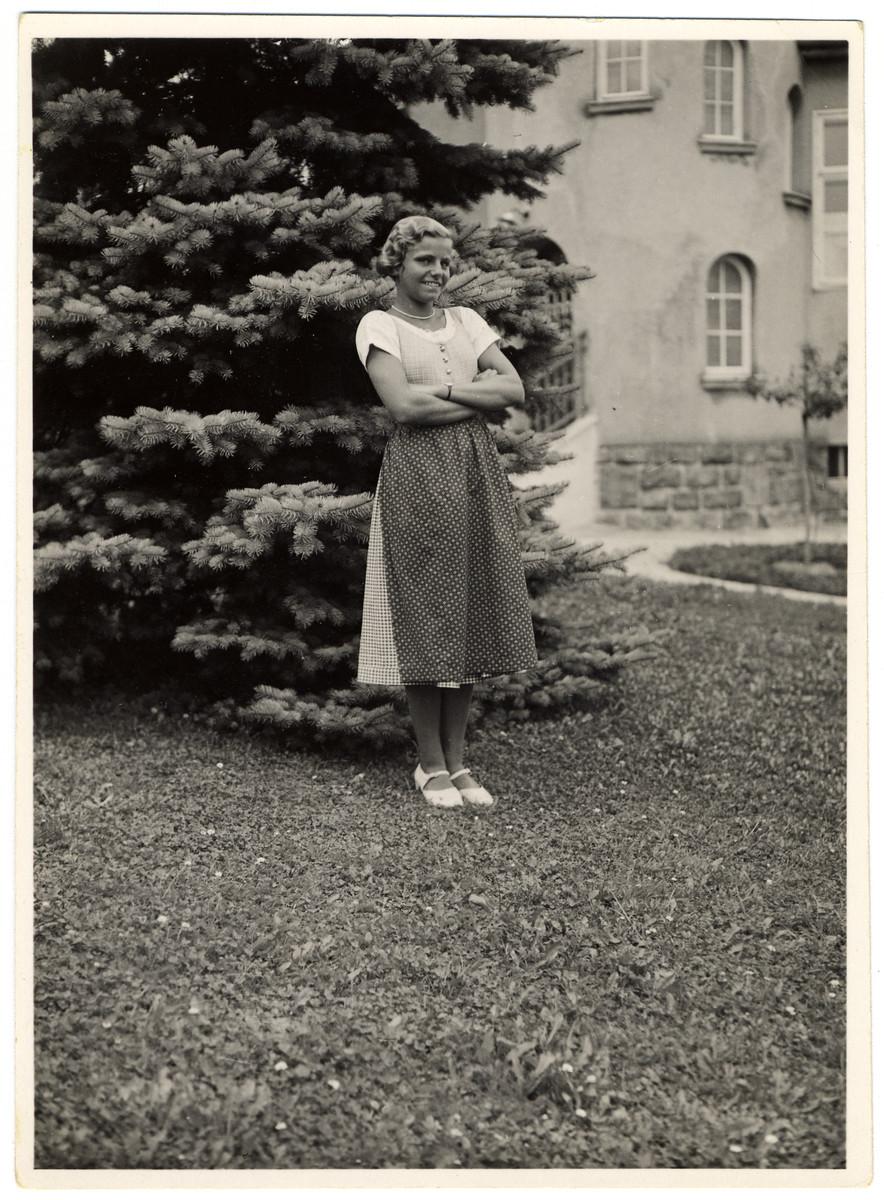 Hedi Politzer stands in a garden wearing a traditional Austrian dress.