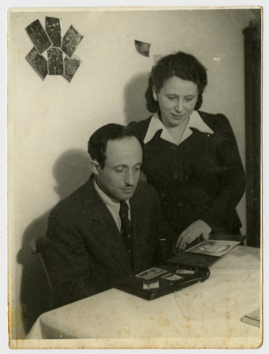 A Jewish couple examines a photo album in the Feldafing displaced persons camp.