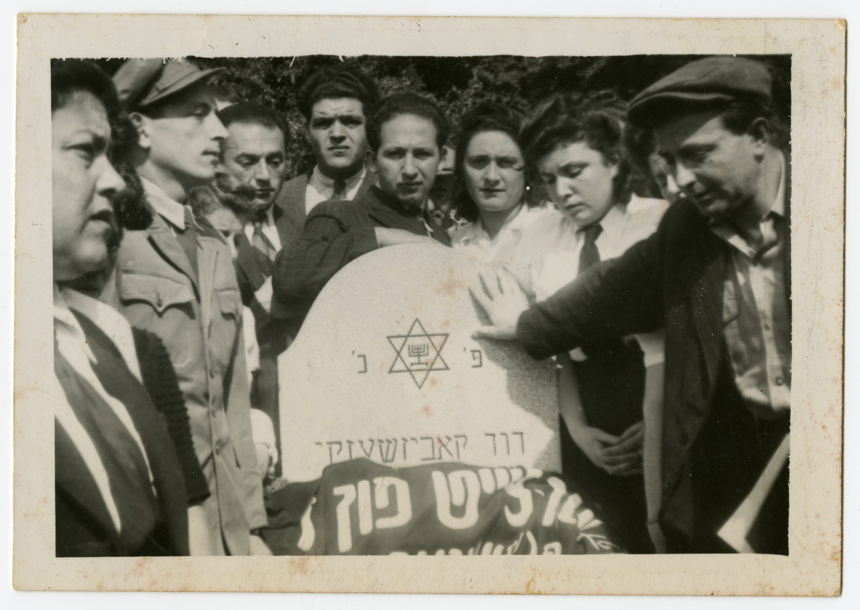 Displaced persons gather around the grave of Jewish policeman, David Kabesicki in Feldafing.  Those pictured include Leib and Jenta Szapiro and Rifka Krasner.