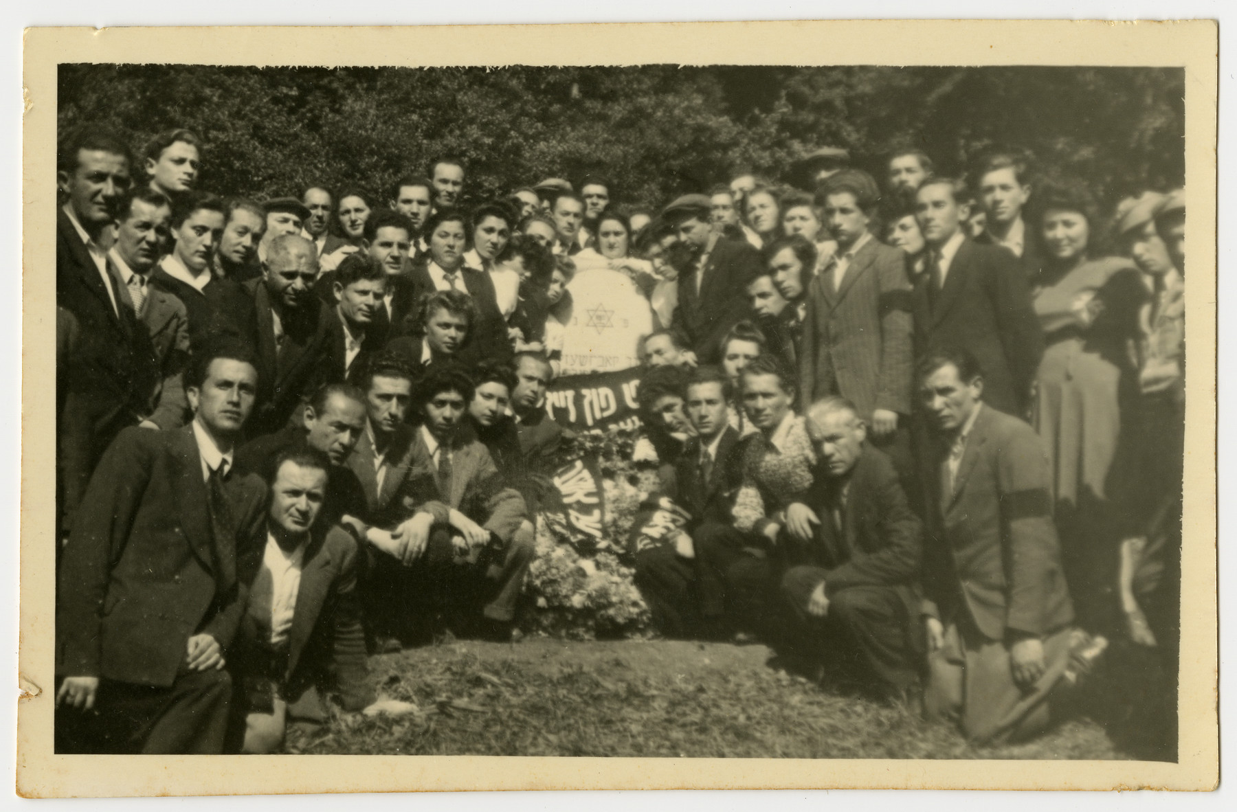 Displaced persons gather in remembrance of the Holocaust victims from Pruzhany, Poland.   In the center is a memorial in the shape of a tombstone, banners and a wreath.