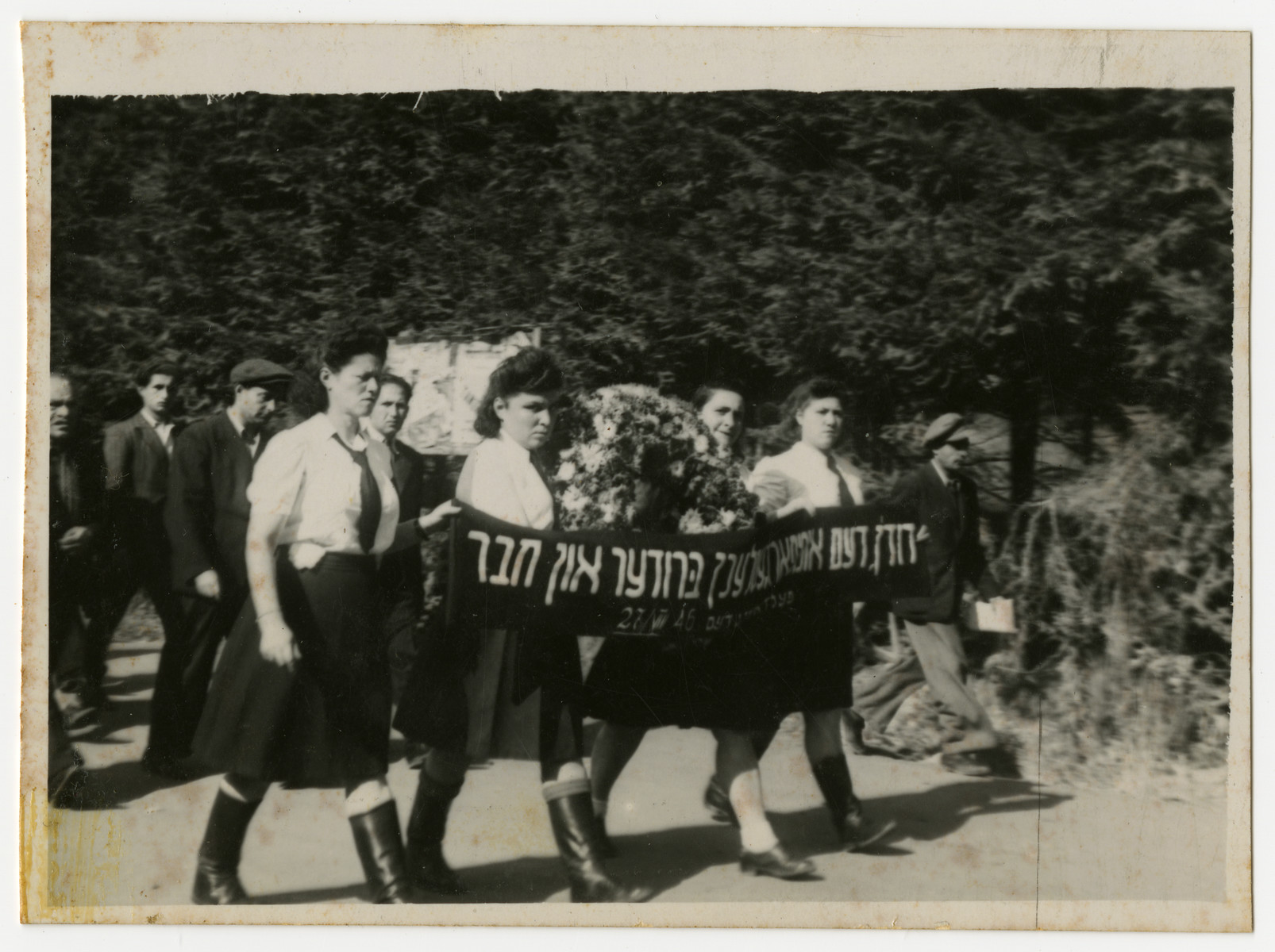 "Women march in a funeral procession carrying a banner in memory of their ""brother and friend""  This is possibly the funeral for David Kabesicki.  Among those pictured are Rifka Krasner (second from the left) and Jenta Szapiro (third from the left)."